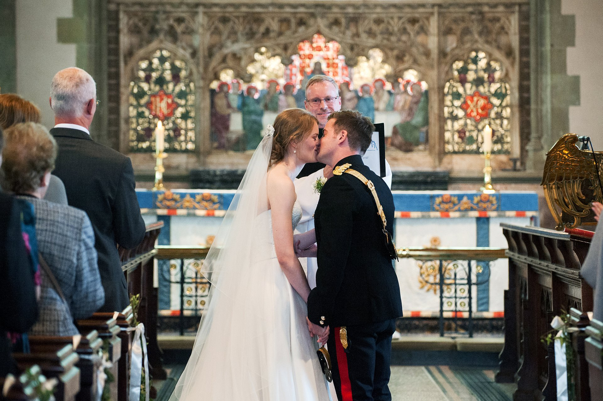 Bride and groom kiss to seal their marriage at St Mary the Vigin Westerham