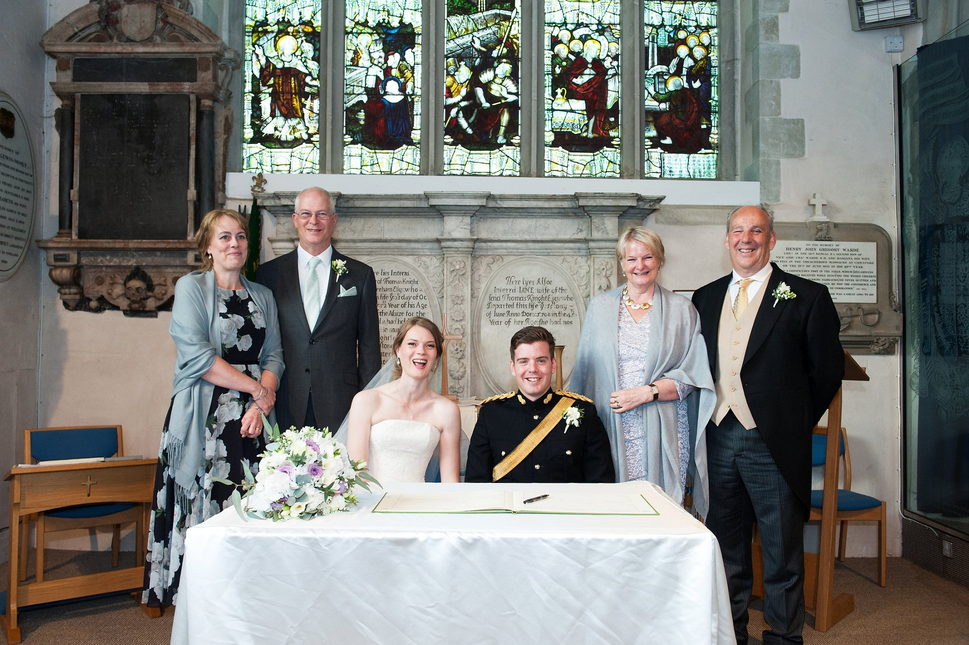 Bride and groom and their parents signing the register at St Mary's Westerham