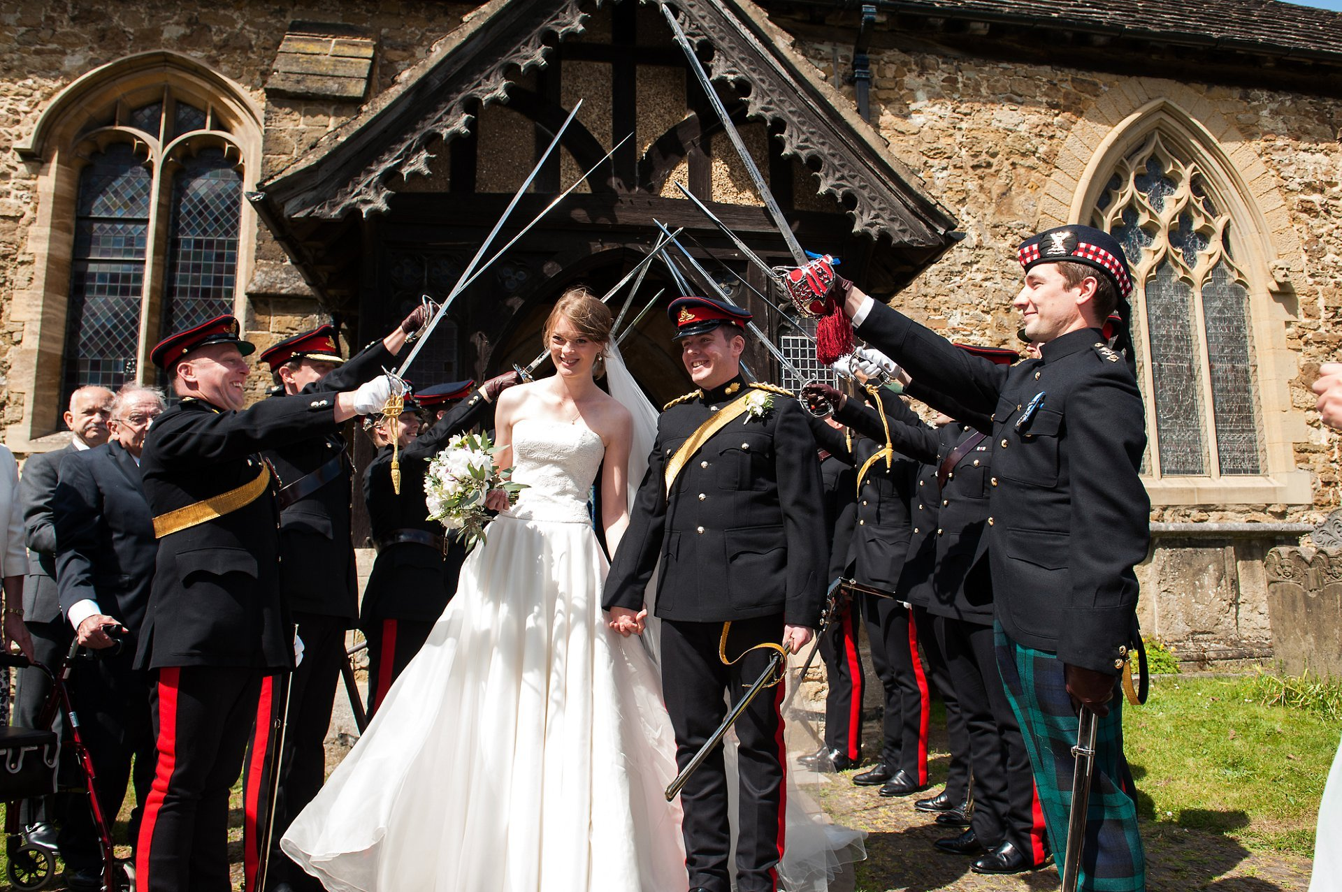 Bride and groom passing under the guard of honour swords outside St Mary the Virgin, Westerham, Kent