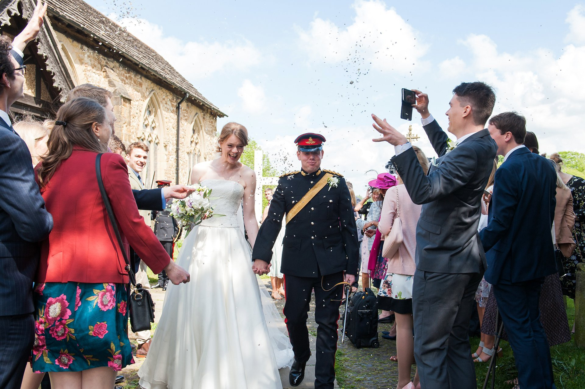 Bride and groom and confetti outside St Mary the Virgin Church, Westerham