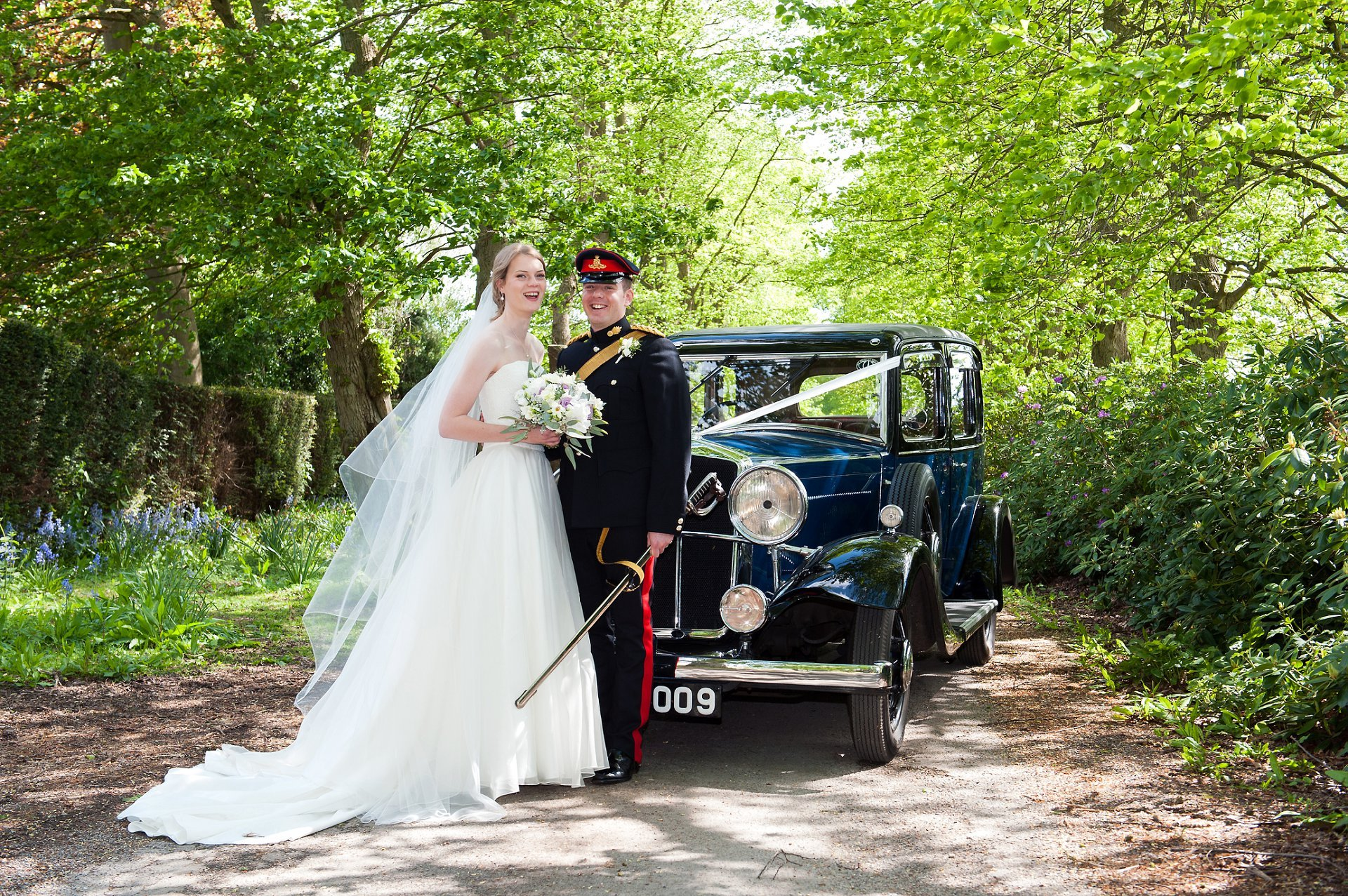 Bride and groom in front of their Wolseley County vintage wedding car with the long tree lined drive of Starborough Mano behind them