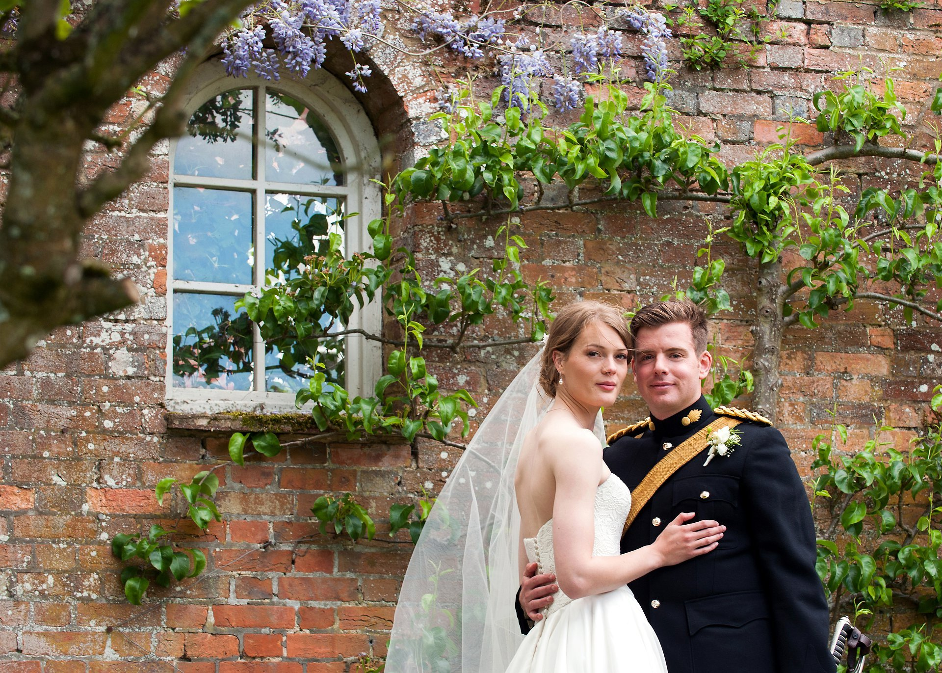 Bride and groom in front of the wisteria at Starborough Manor