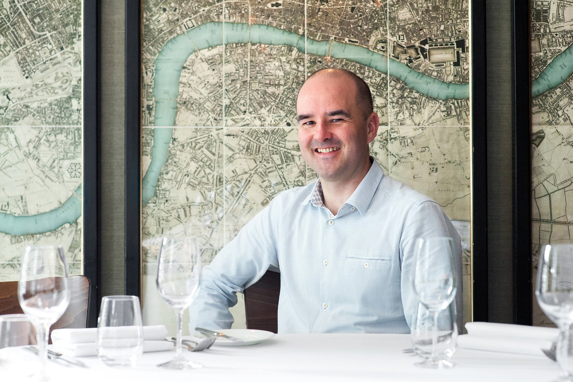 Chelsea Restaurant Medlar - David O'Connor, co-owner and front of house at Medlar in front of the impressive map triptych in the private dining room