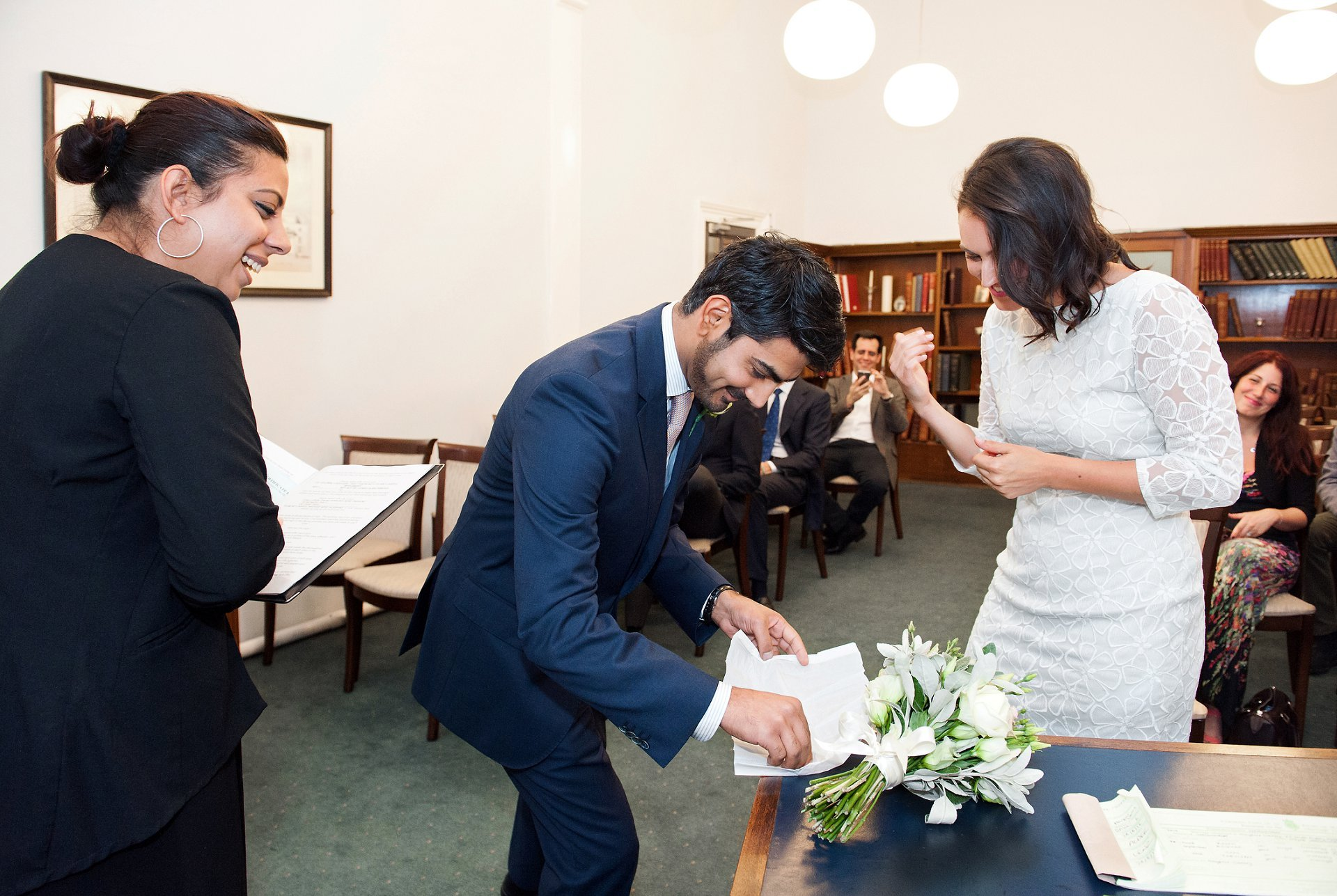 Mayfair Library wedding photography by Emma Duggan in the elegant Marylebone Room with the groom here picking up the wedding band to exchange rings with his bride to be