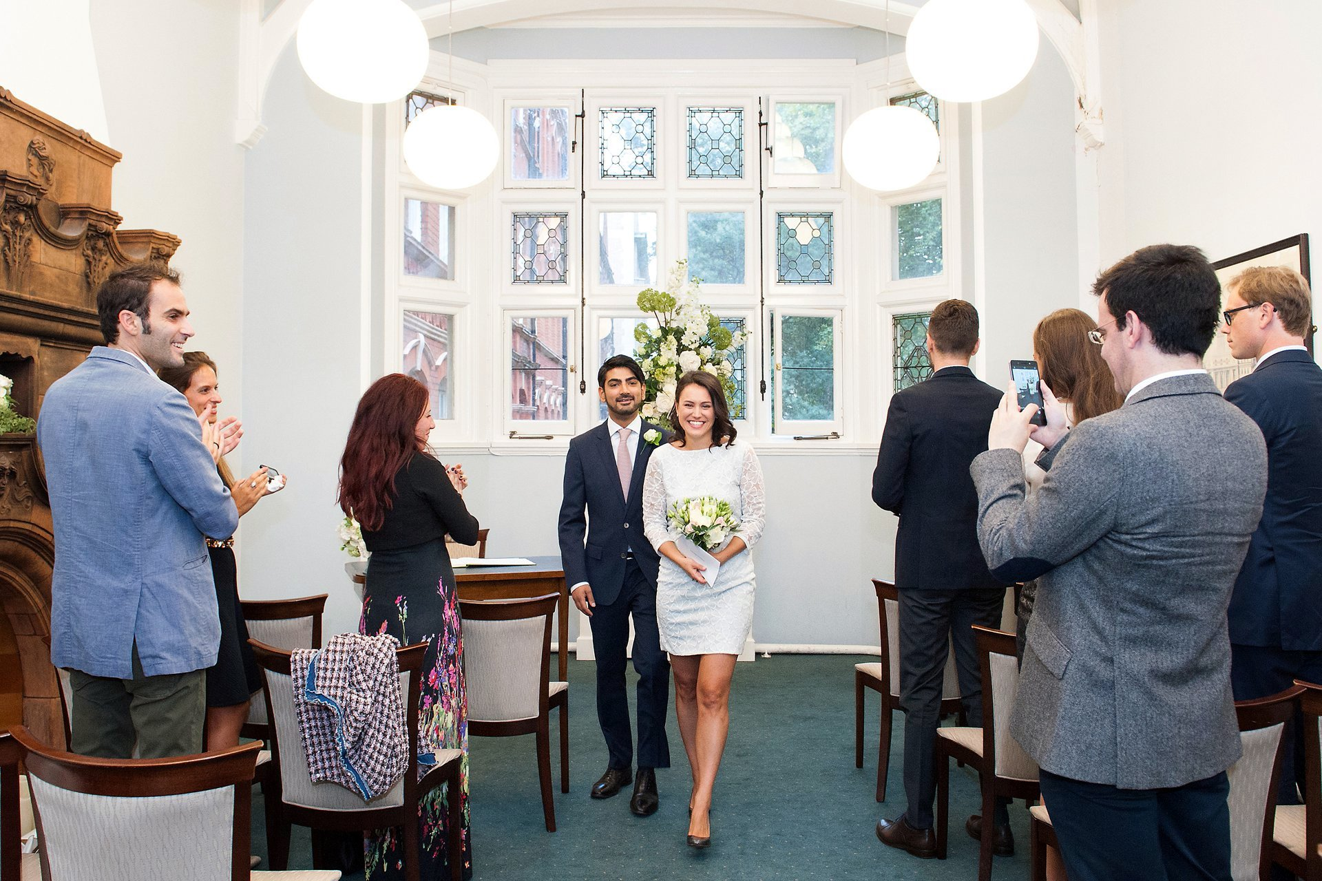 Bride and groom leaving the Marylebone Room inside Mayfair Library as huband and wife