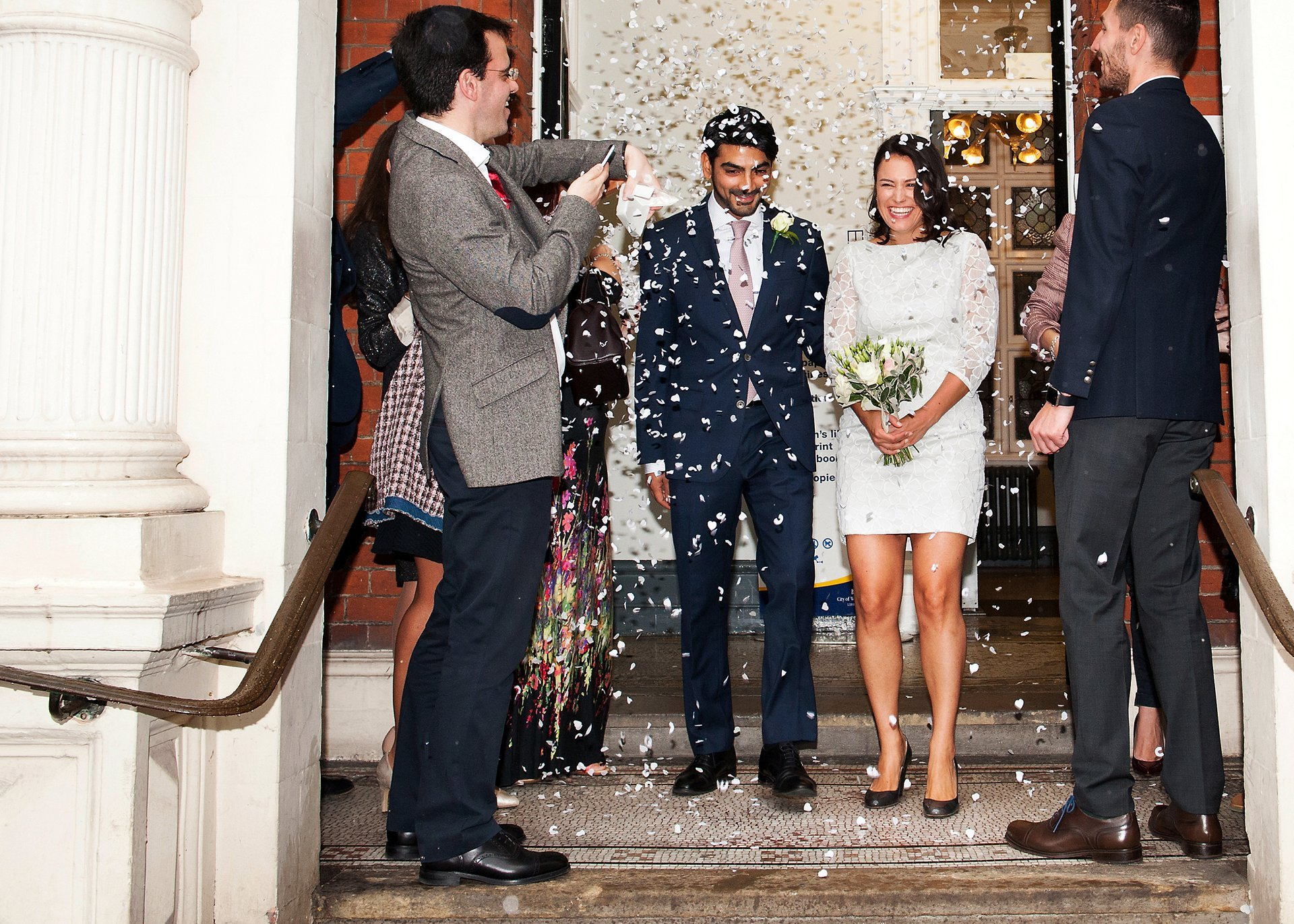 The bride and groom leaving Mayfair Library with guests throwing confetti inside the porch due to the heavy rain outside