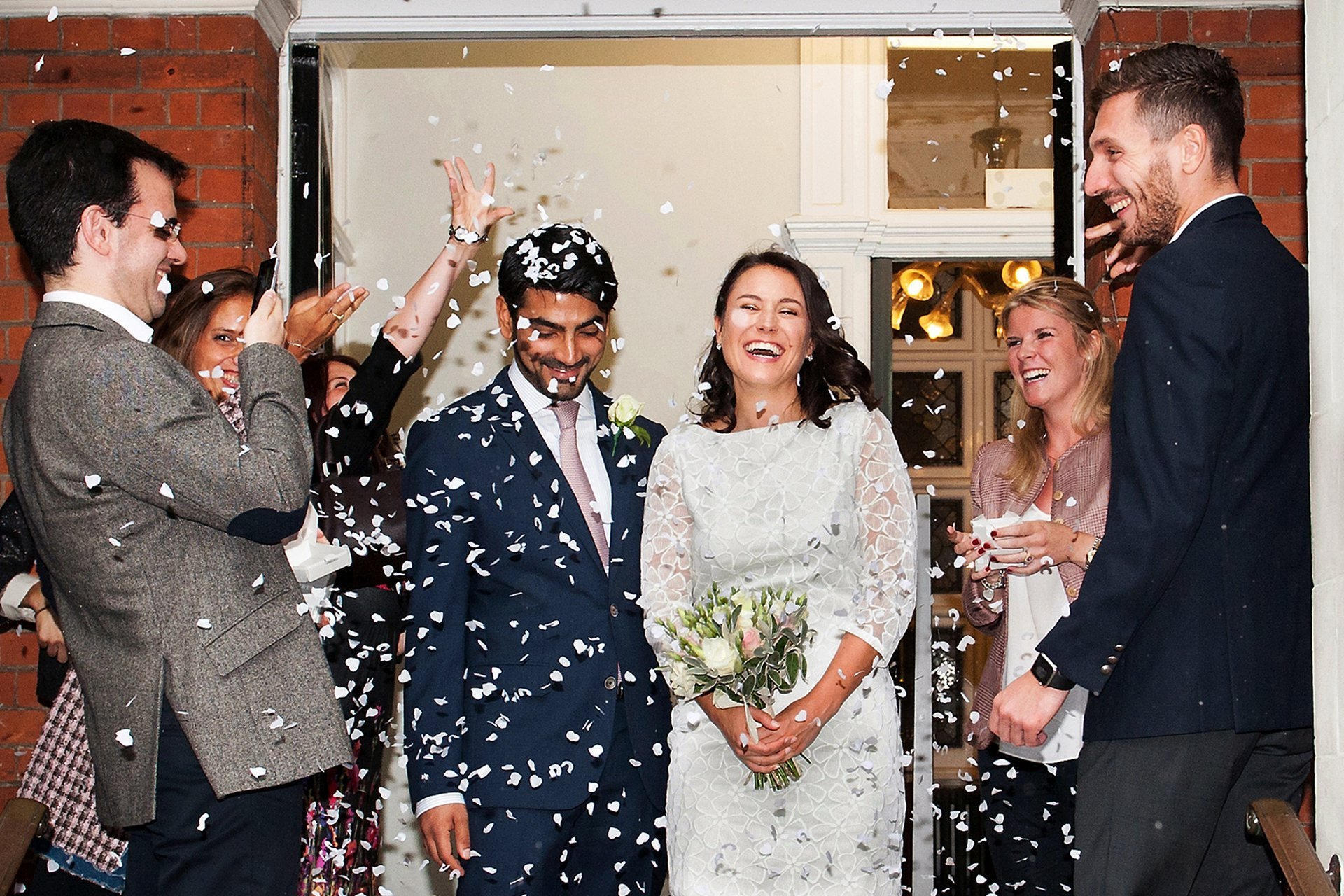Mayfair Library rainy wedding photography - guests throwing confetti inside the porch at Mayfair Library due to the monsson-like heavy rain outside