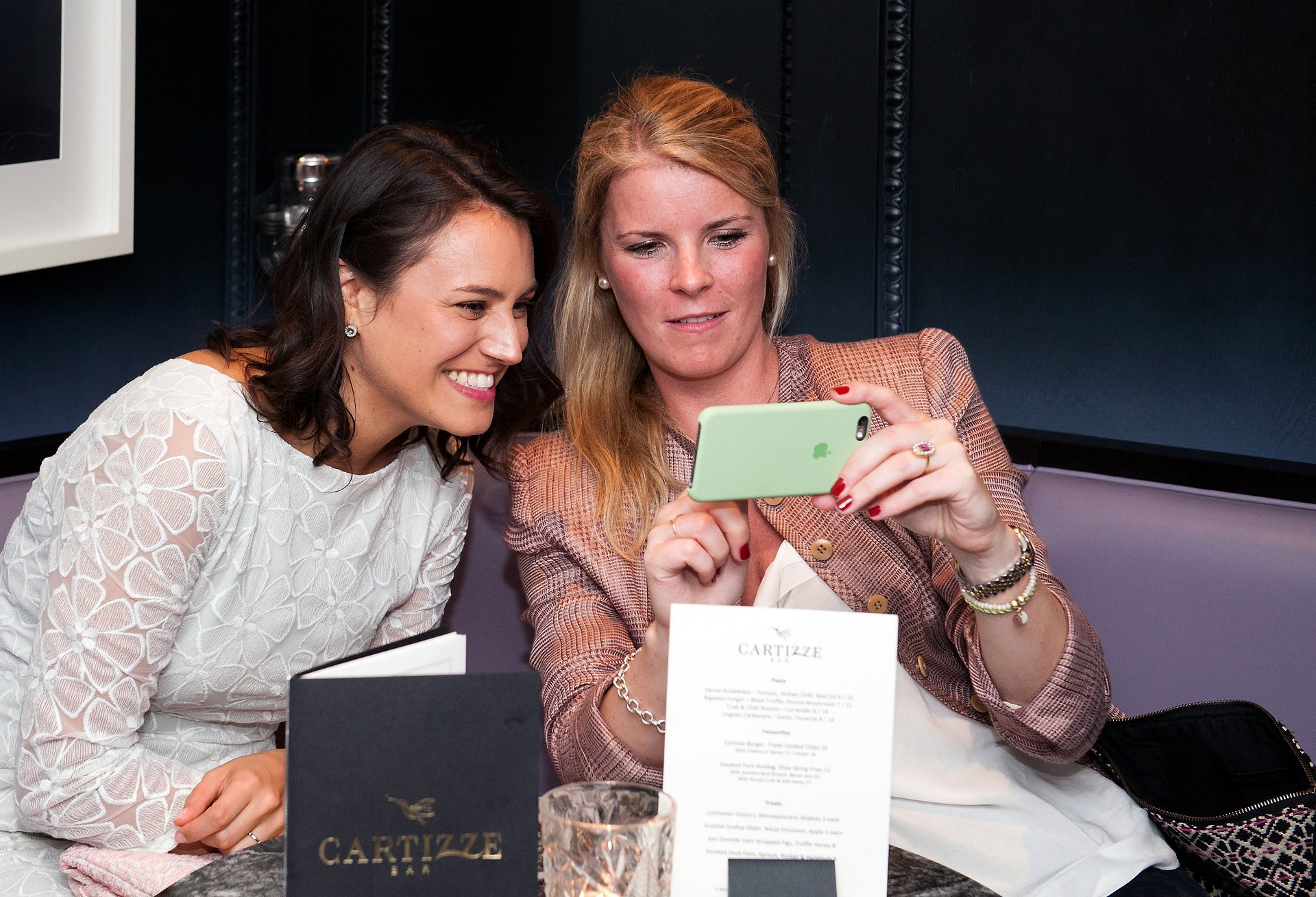 Bride and her friend sharing photos of their Mayfair Library wedding ceremony in Cartizze bar