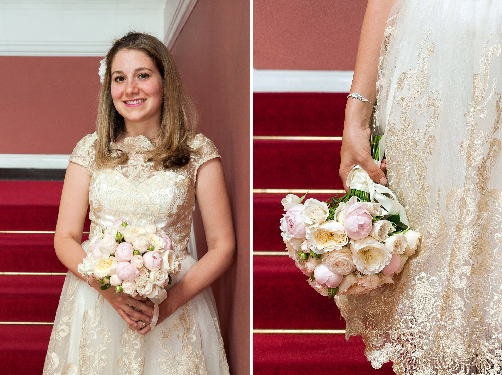 The bride on the red staircase inside Chelsea Old Town Hall in a mid-length ivory sweatheart neck tulle dress with gold lace overlay and small sleeves. She is holding a bouquet of pale pink peonies and cream roses