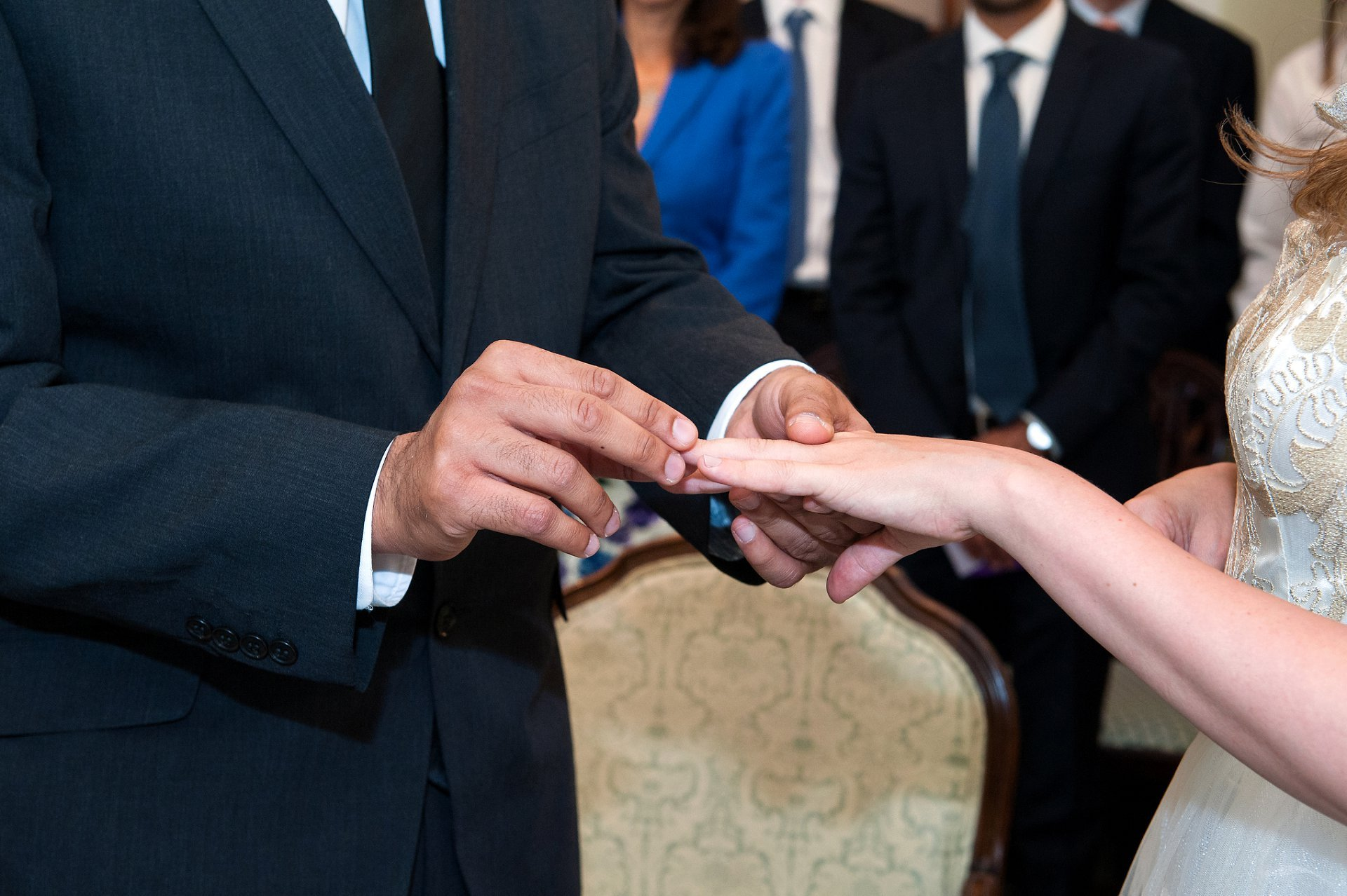 The groom places the wedding band on his bride's finger during this Chelsea wedding