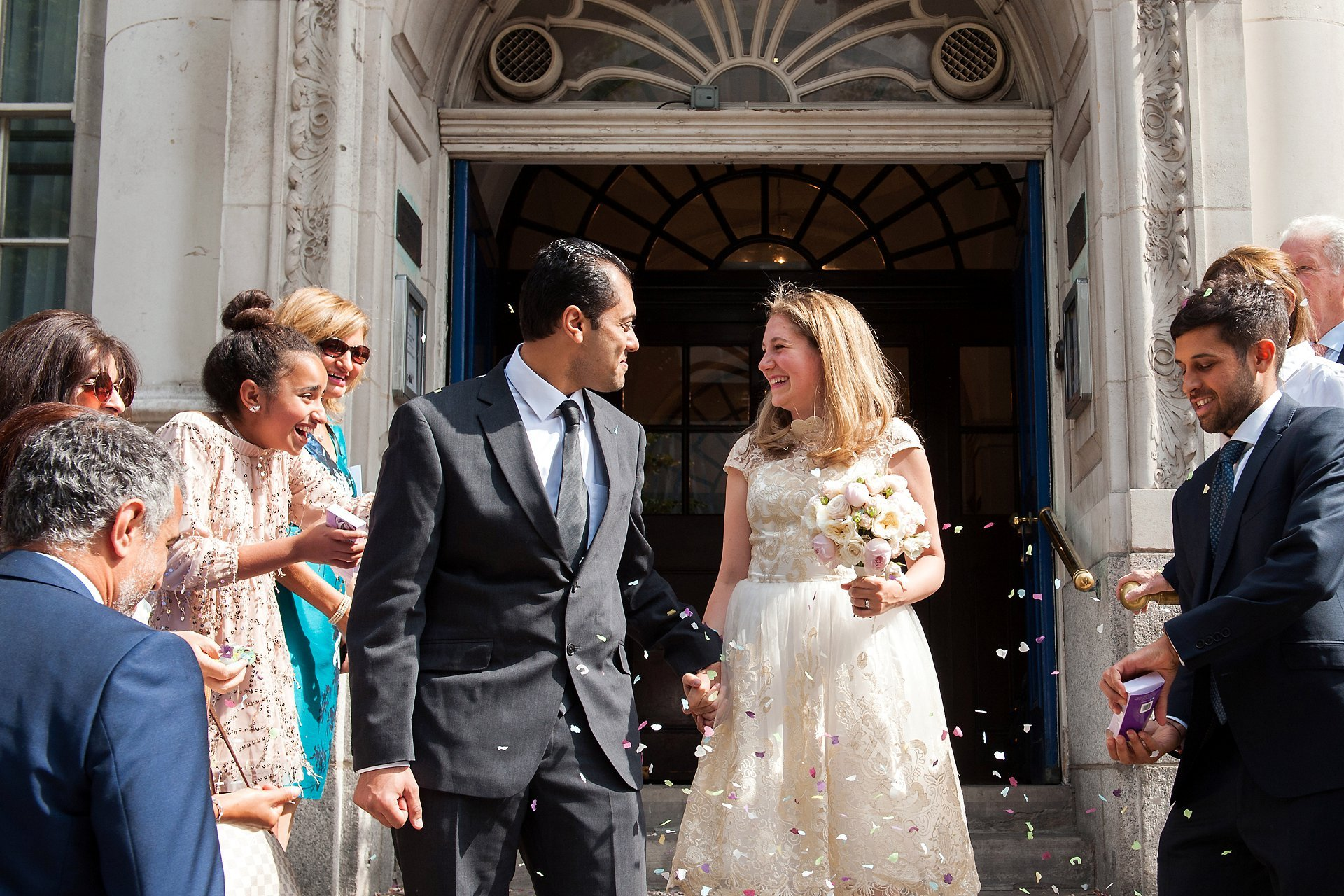 The bride and groom smile at each other on Chelsea Old Town Hall's famous steps