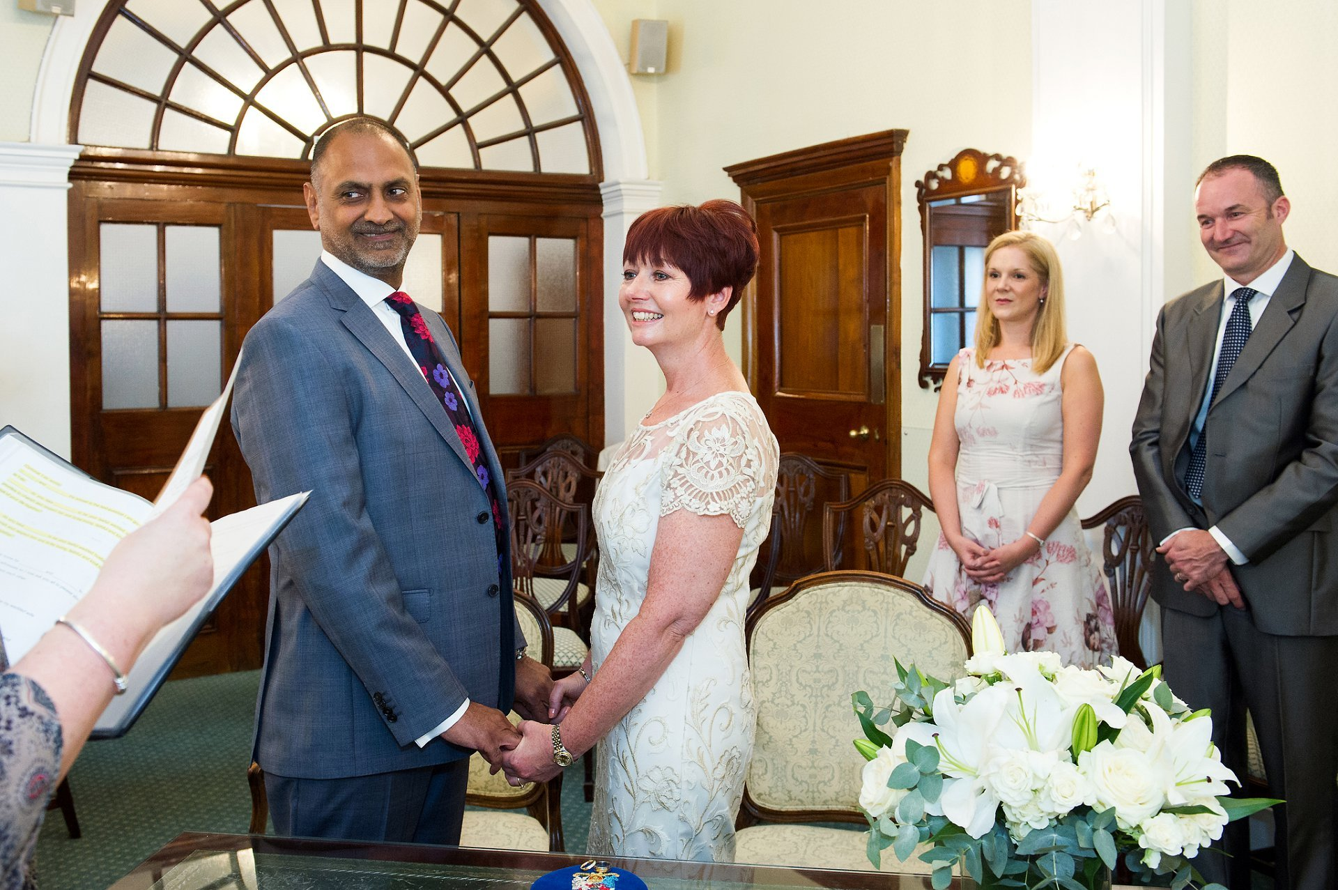 The bride and groom look towards the Chelsea Registrar during their civil marriage ceremony