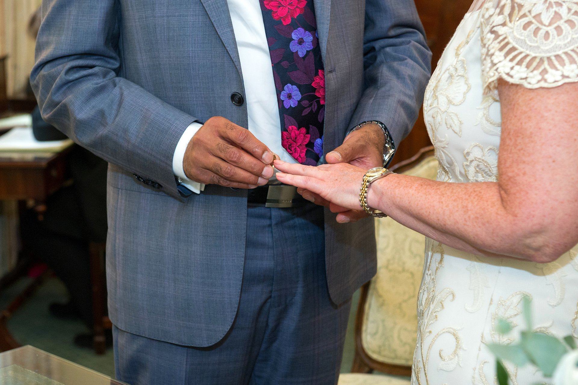 The groom places the wedding ring on his bride's finger during this Chelsea wedding ceremony