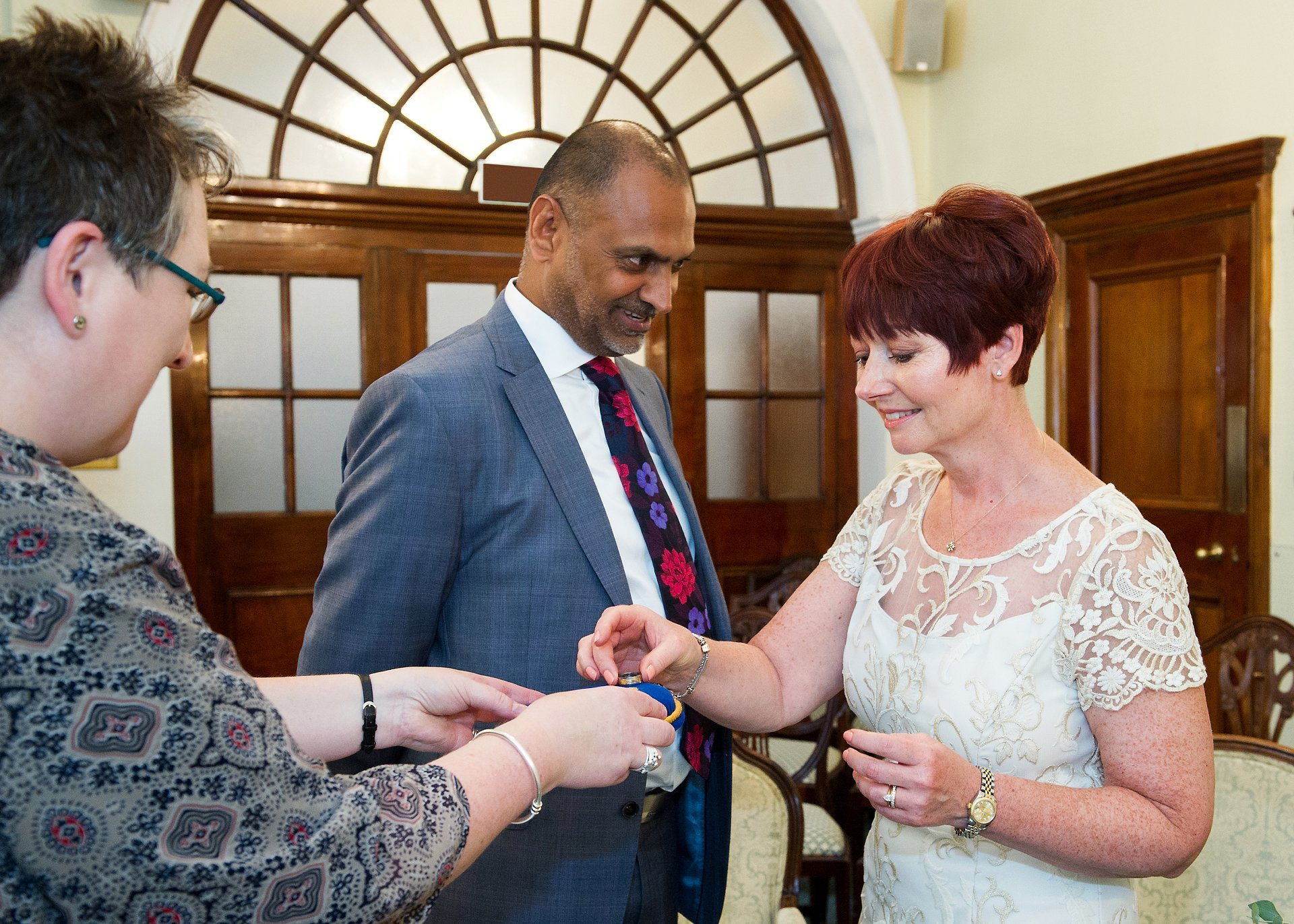 Chelsea Old Town Hall wedding photographer Emma Duggan photographs a couple marrying in the Rossetti Room of the Kensington & Chelsea Register Office with the groom smiling as his bride takes the wedding band from the Registrar