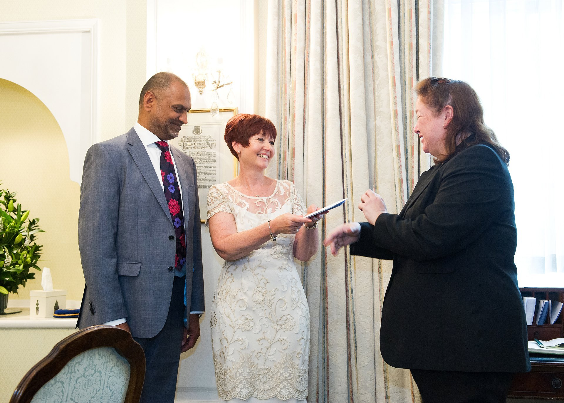 Chelsea registry office wedding photography by a register office specialist here showing the bride and groom receiving their marriage license to the bride
