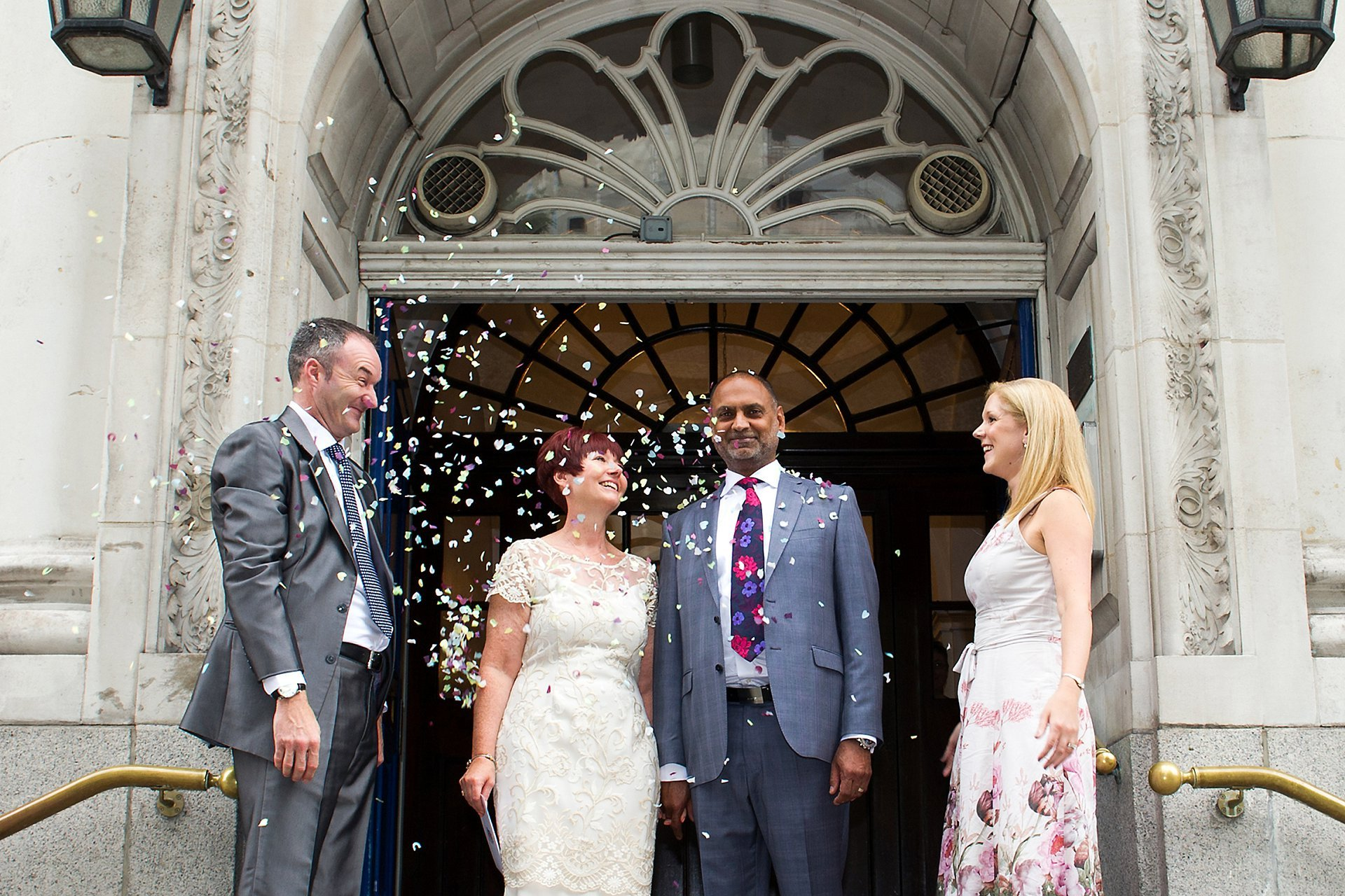 Register office wedding photography on the famous King's Road steps of the Kensington & Chelsea Register Office (Chelsea Old Town Hall) with the couple and their two guests and confetti