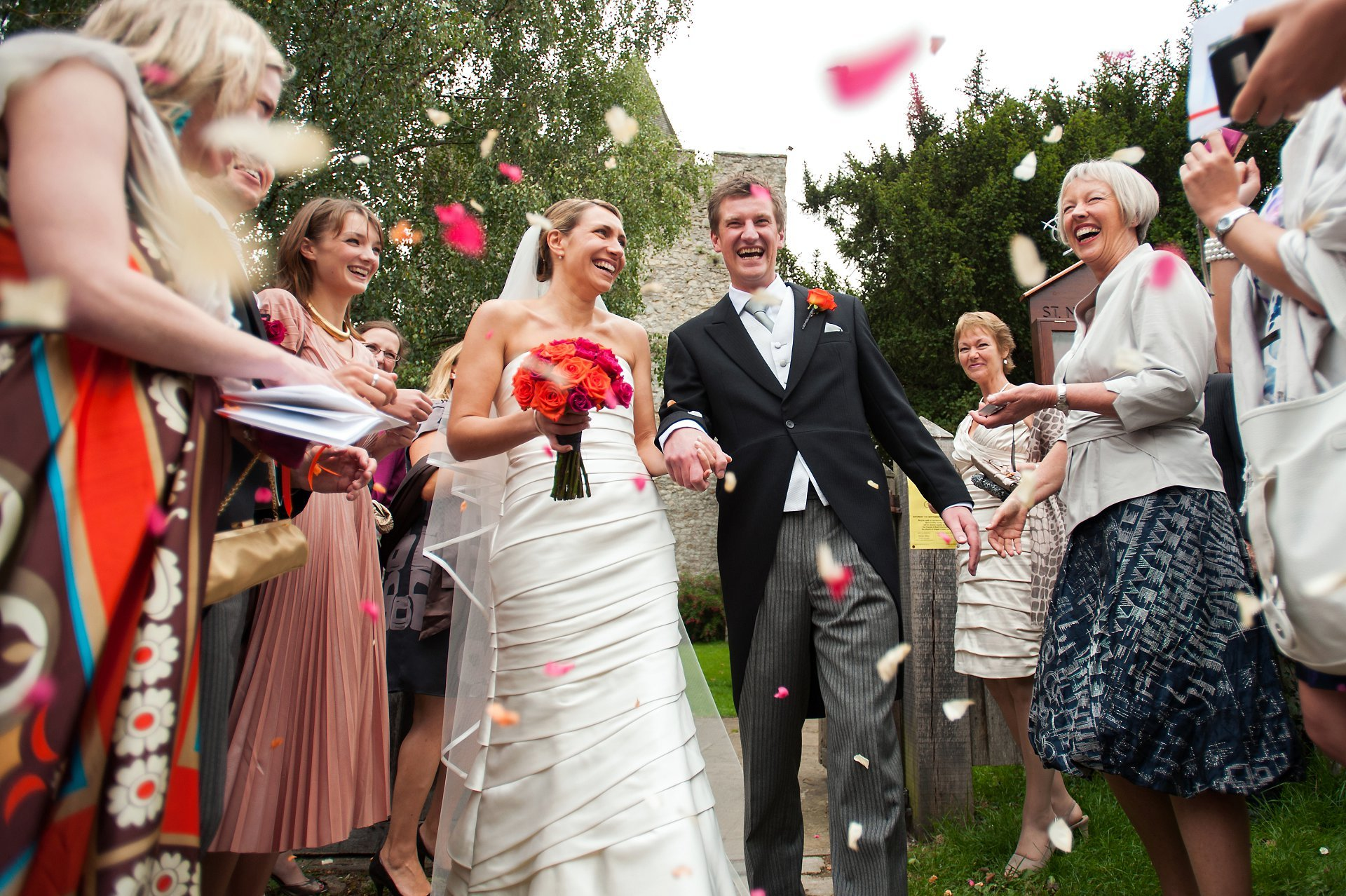 Leeds Castle Autumn Wedding photographer by Leeds Castle wedding photographer Emma Duggan - here the happy couple are leaving St Nicholas Church in Leeds Village with close friends and family throwing confetti