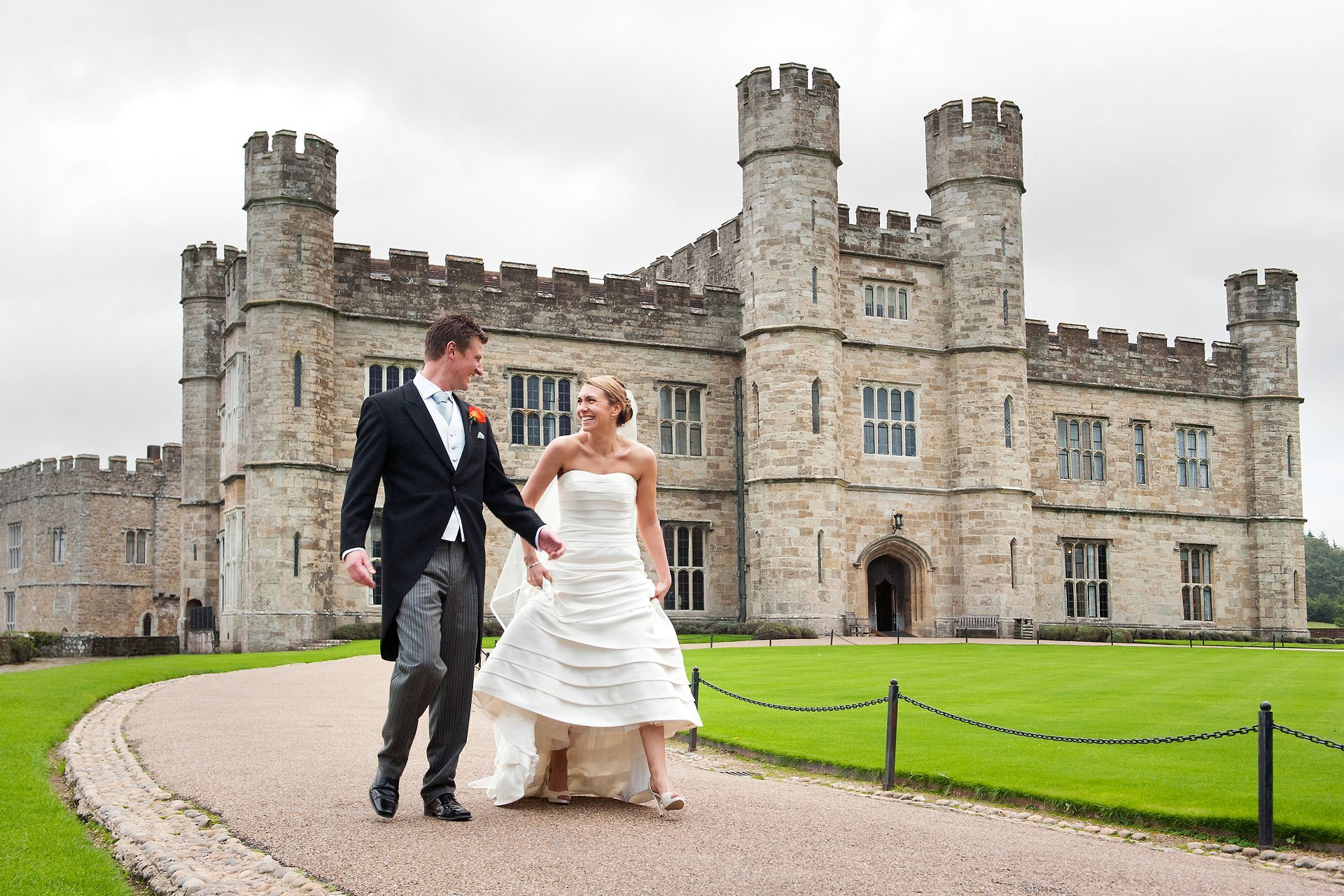 Leeds Castle Autumn Wedding for Leeds Castle wedding photogrpahy by specialist Emma Duggan Photography who offers small wedding coverage from just one hour here the bride and groom are walking in front of Leeds Castle after their church wedding in nearby Leeds Village
