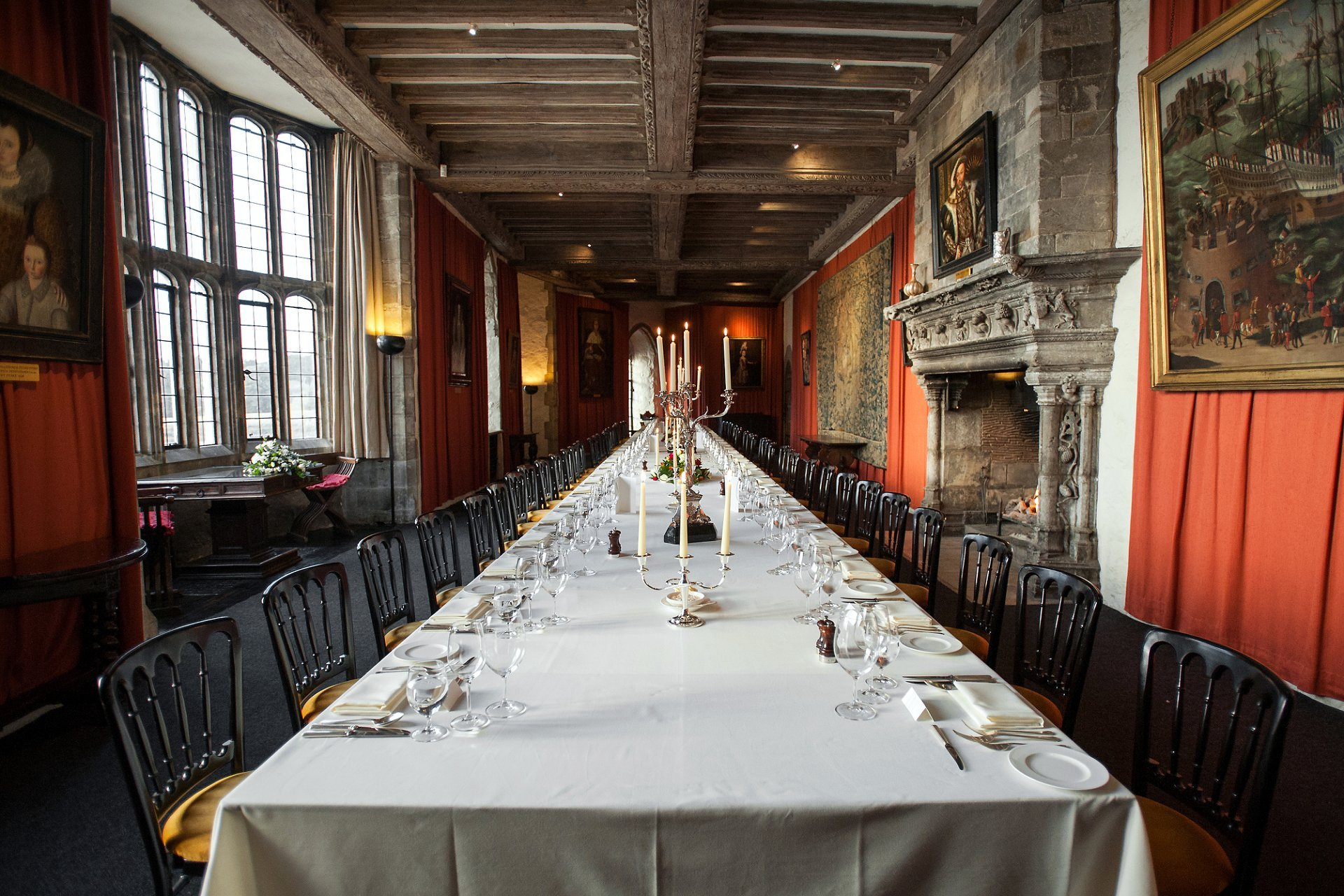 The Henry VIII Banqueting Hall laid for a wedding breakfast with simple table settings and elaborate silver candelabras