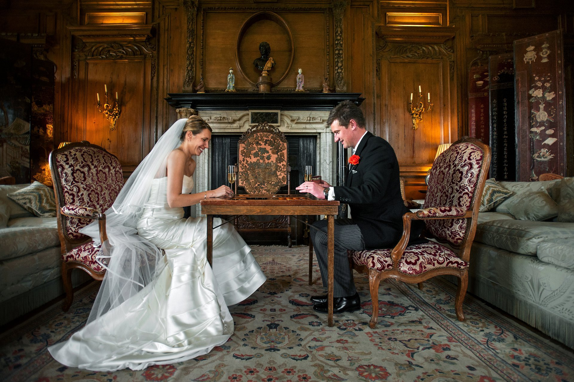 The bride and groom play backgammon in the Thorpe Hall Drawing Room at Leeds Castle on their wedding day