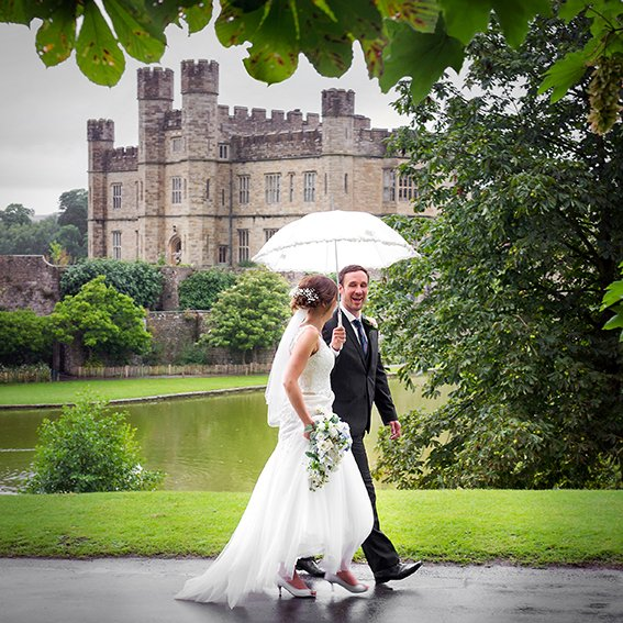 Leeds Castle wedding photographer Emma Duggan Photography captures Leeds Castle in the summer rain with a bride and groom walking with a white umbrella at this historic Kent venue also known as the loveliest castle in the World