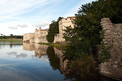 Wedding photography at Leeds Castle in early Autumn with still cold water surround the Castle main buildings