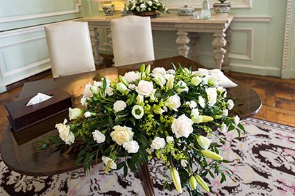 The signing of the register table in the Ceremony Room at Leeds Castle with stunning cream and green flowers