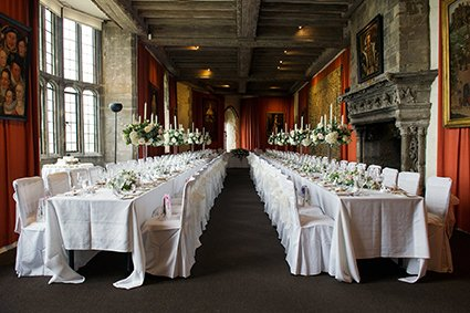 Leeds Castle's Henry VIII dining room laid for 80 guests with tall vases