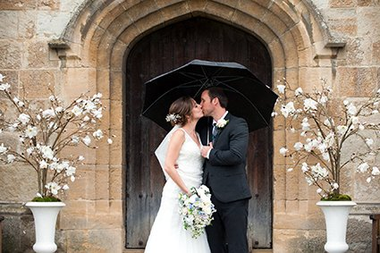 The main wooden entrance doors to Leeds Castle with magnolia trees either side and the bride and groom in rain kissing just outside