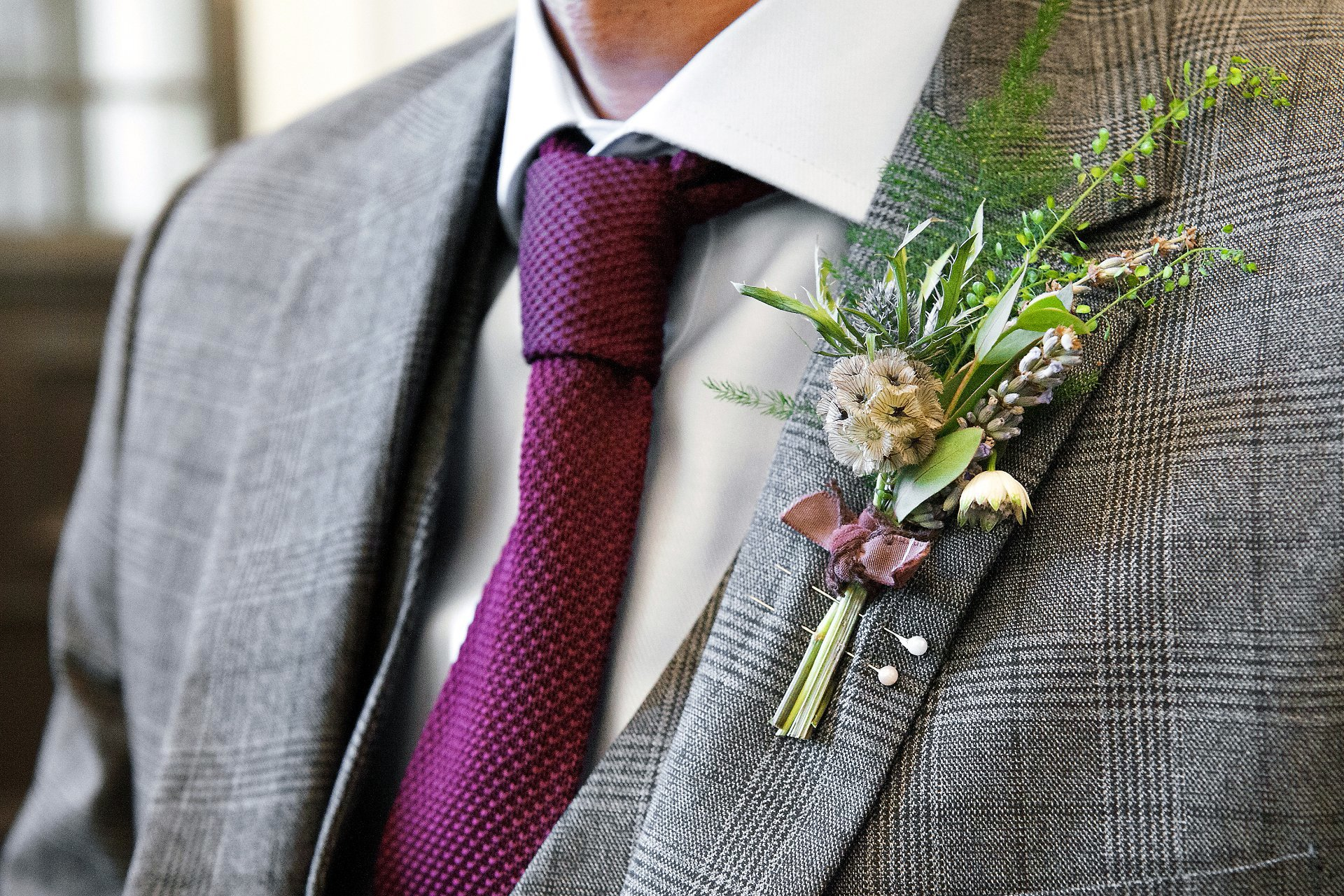 The groom, Adrian, in a grey three-piece Prince of Wales check suit with purple tie and wild flower buttonhole provided by Grace & Thorn florist in Hackney