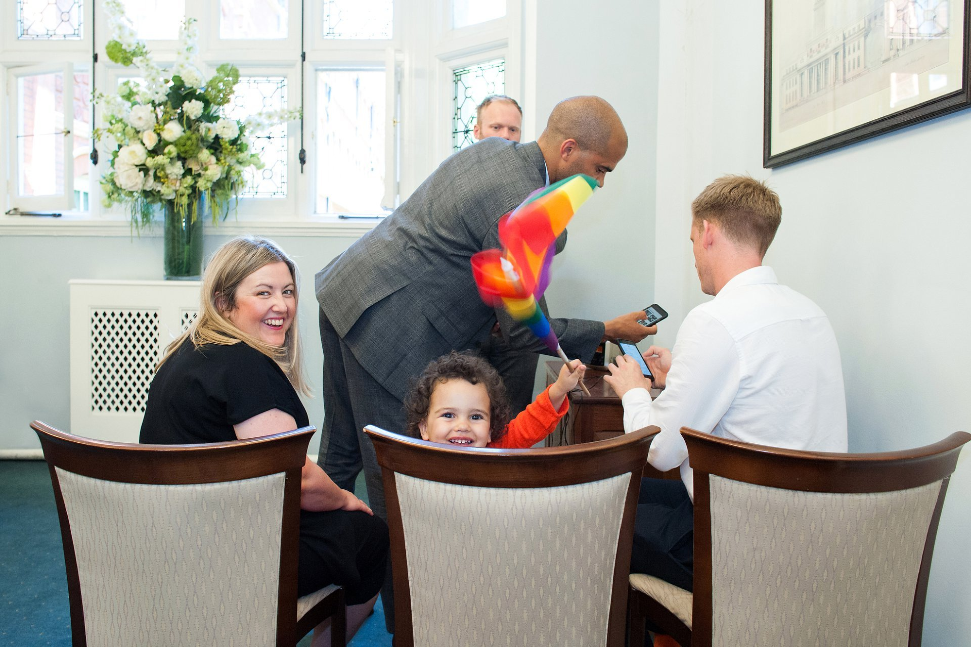 The flowergirl and couple's daughter waves her Pride in London rainbow flag just before her parents marry at Mayfiar Library