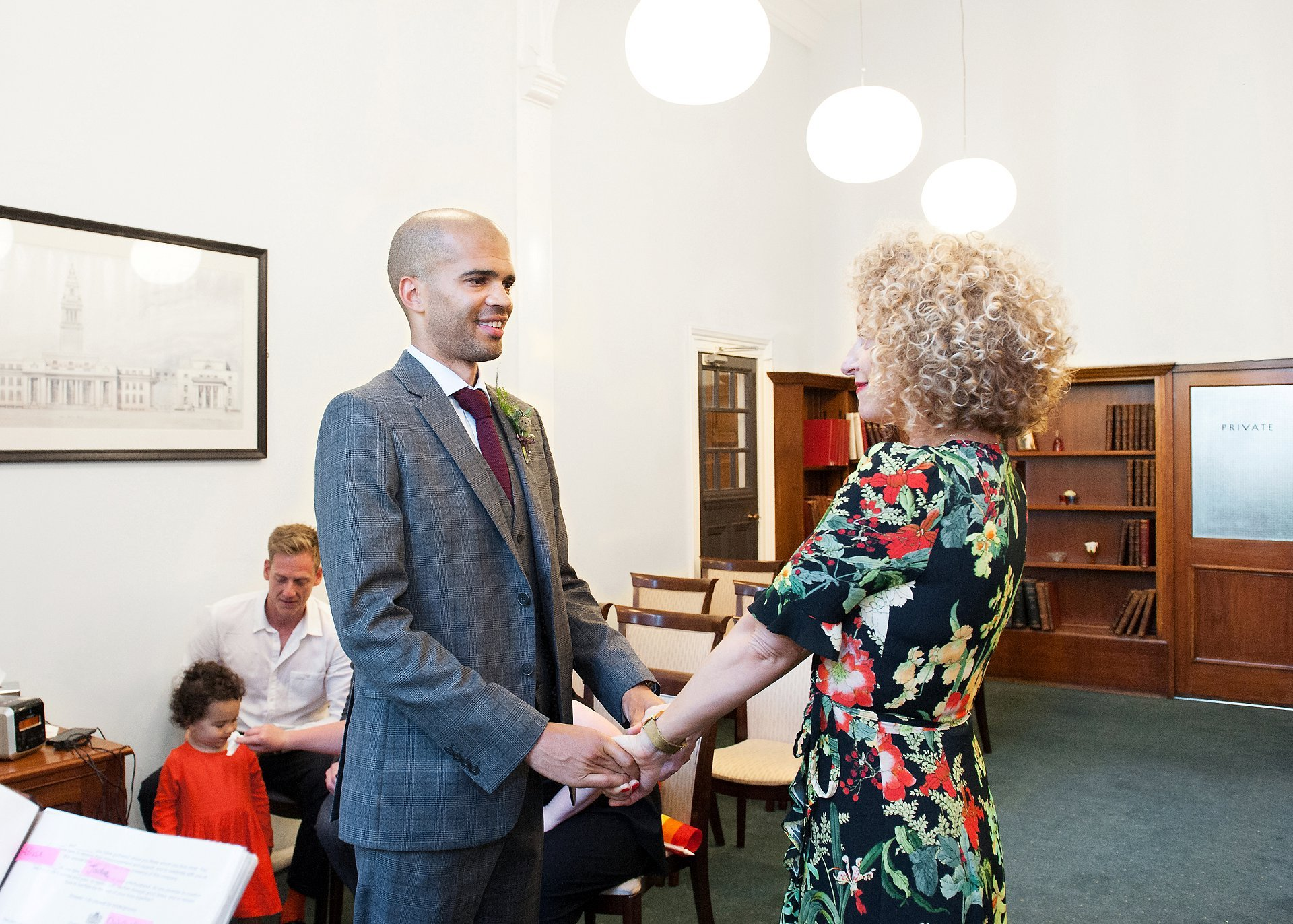 Bride & groom complete their vows in the Marylebone Room at Mayfair Library and smile reassuringly at each other