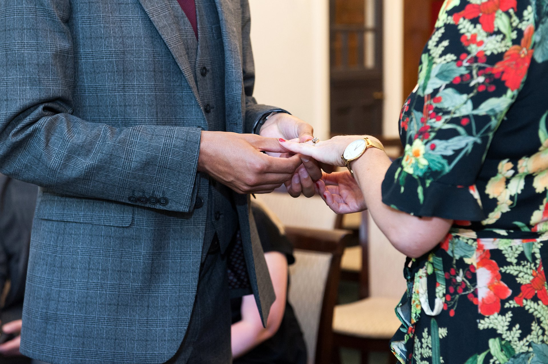 The groom exchanges rings with his new wife at this festive Mayfair Summer wedding