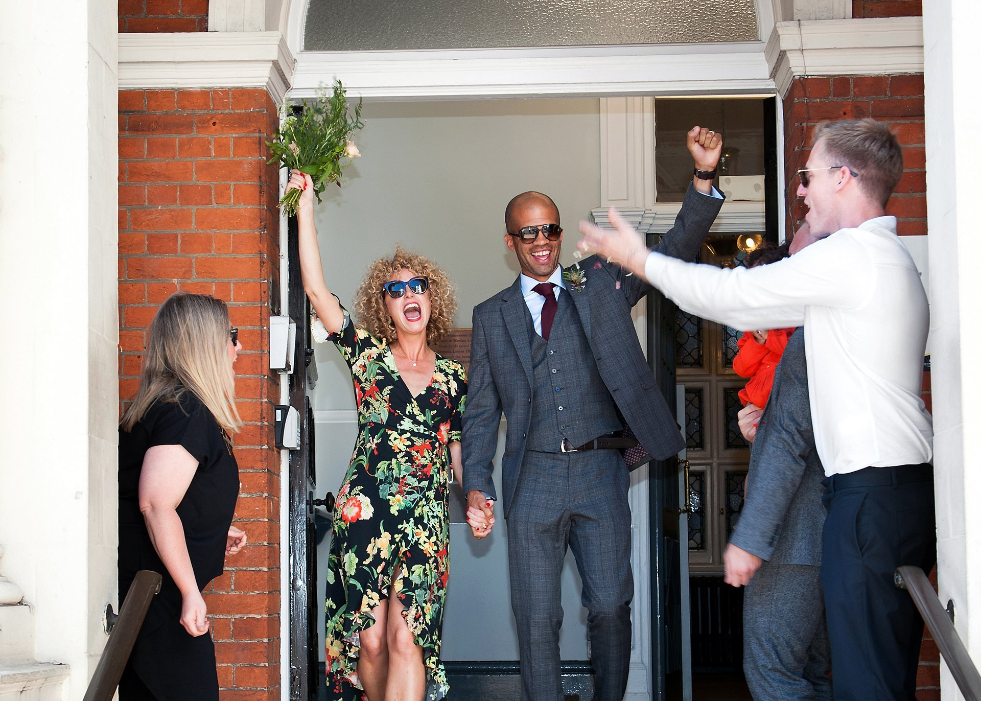 The bride and groom exit Mayfair Library wearing sunglasses with arms aloft and guests throwing confetti