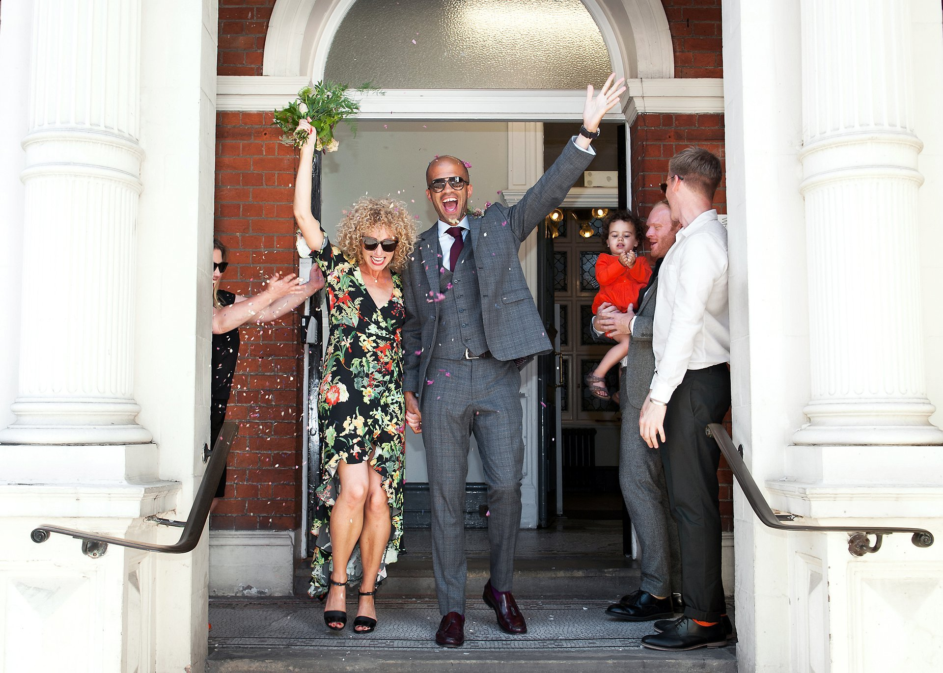 London wedding photographer Mayfair Library - a couple leaving Mayfair Library, wearing shades, holding their arms aloft in celebration of their Westminster Register Office wedding