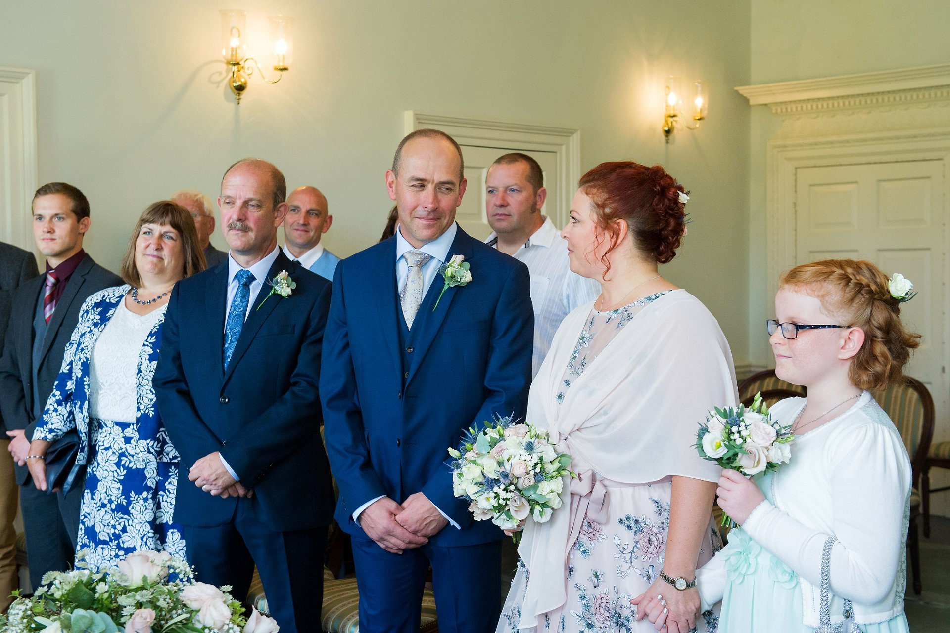 The Drawing Room ceremony room at Park House in Horshamhere showing the bride and groom and their wedding guests at the start of their civil wedding ceremony