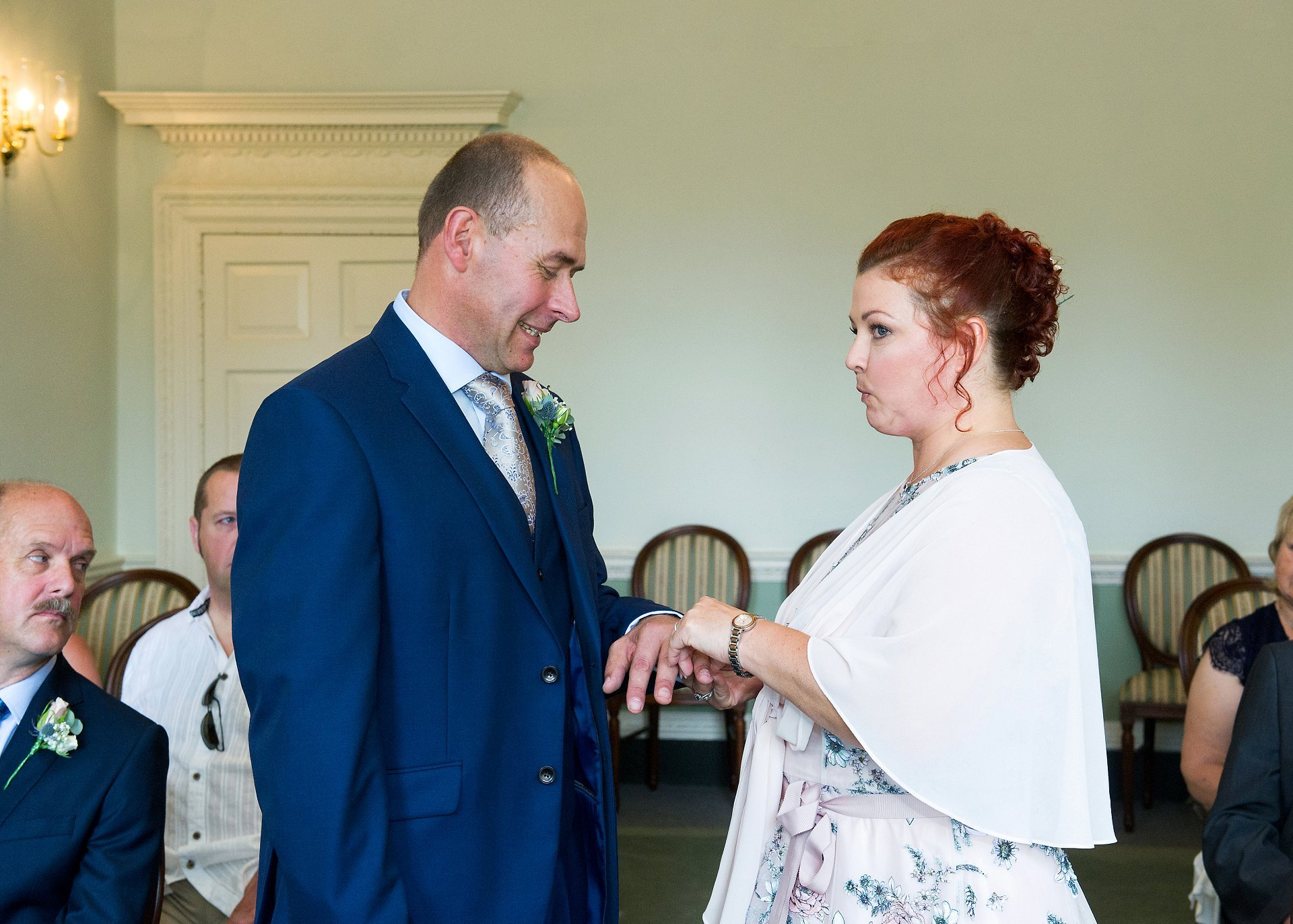 The Drawing Room ceremony venue at Horsham Register Office with a bride and groom exchanging rings and the bride giggling