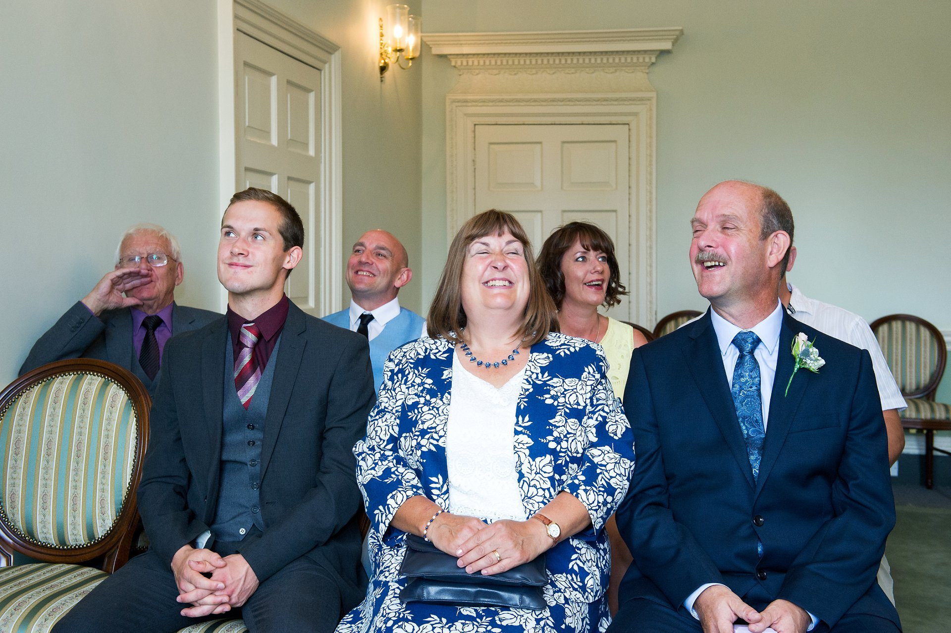 Guests in the Drawing Room ceremony venue at Park House in Horsham laughing as the bride and groom exchange their wedding vows