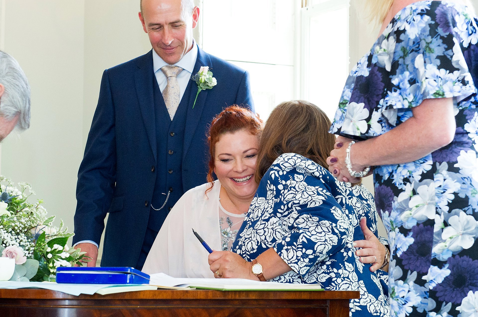 A guests congratulates the bride during the signing of the register at Park House Registry Office in Horsham