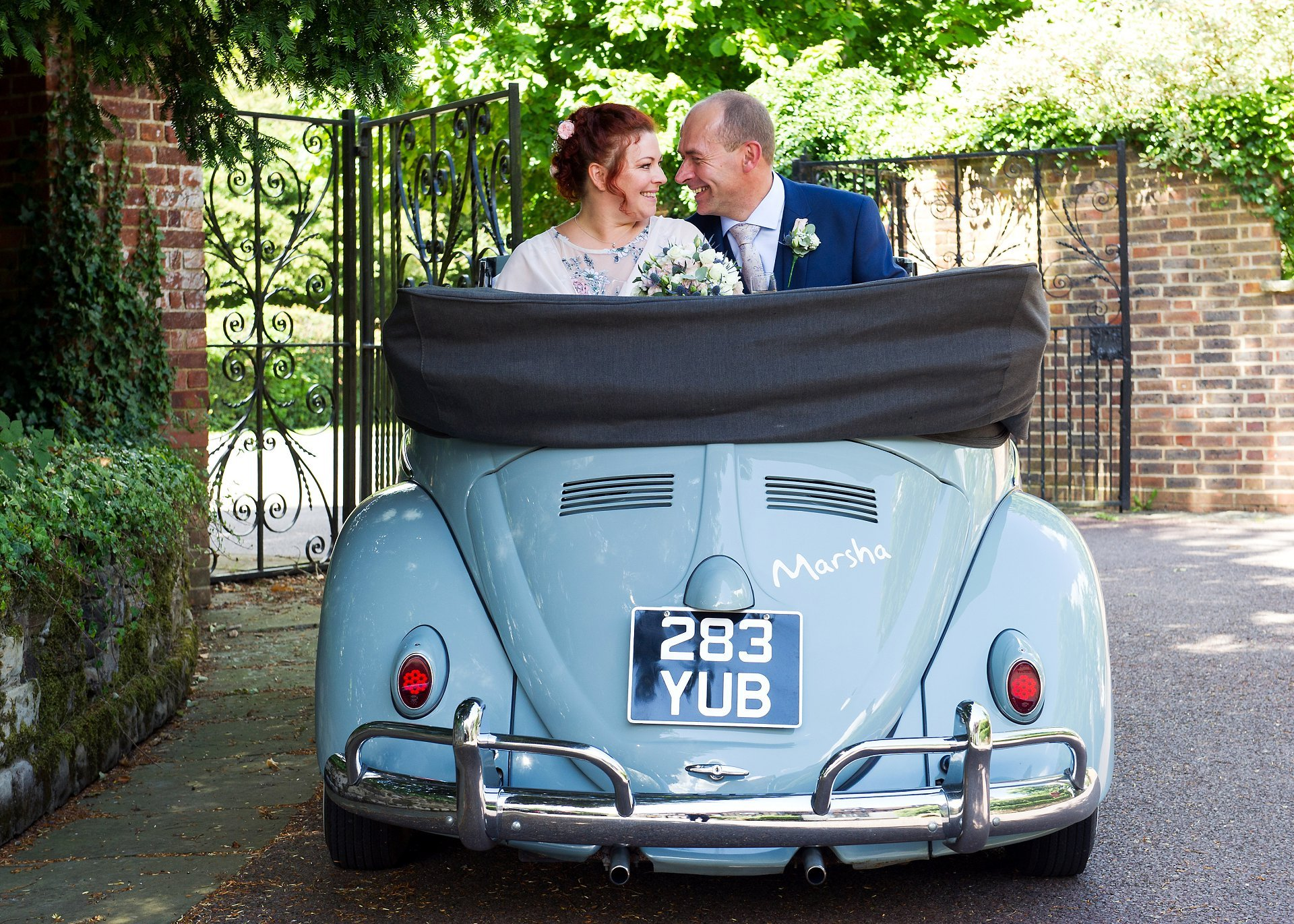 Bride and groom in their VW Beetle wedding car just after their Horsham Registry Office wedding having arrived at their reception venue, Ghyll Manor in Rusper