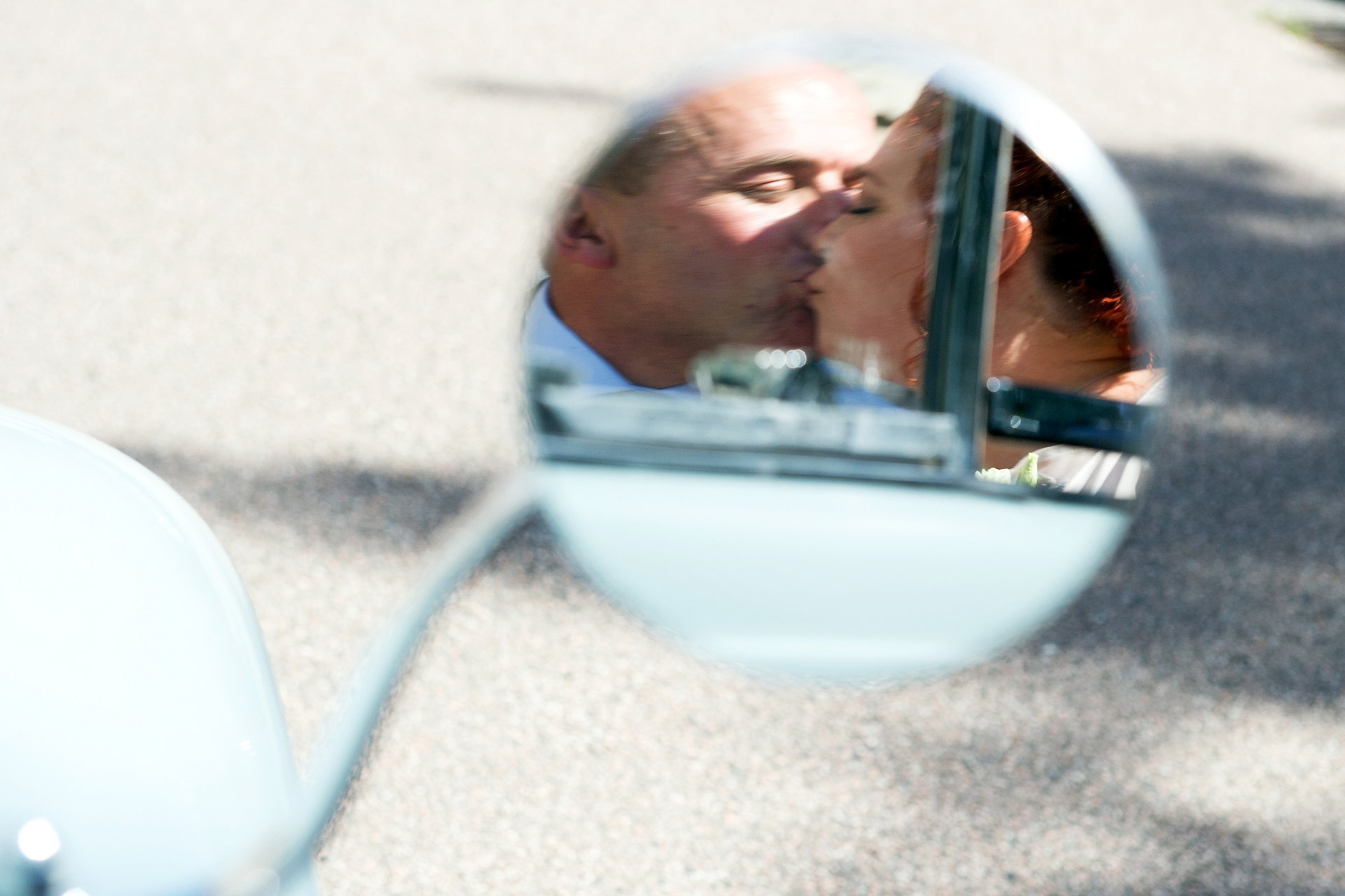 A reflection of the bride and groom in the wingmirror of their VW Beetle edding car at Ghyll manor in West Sussex