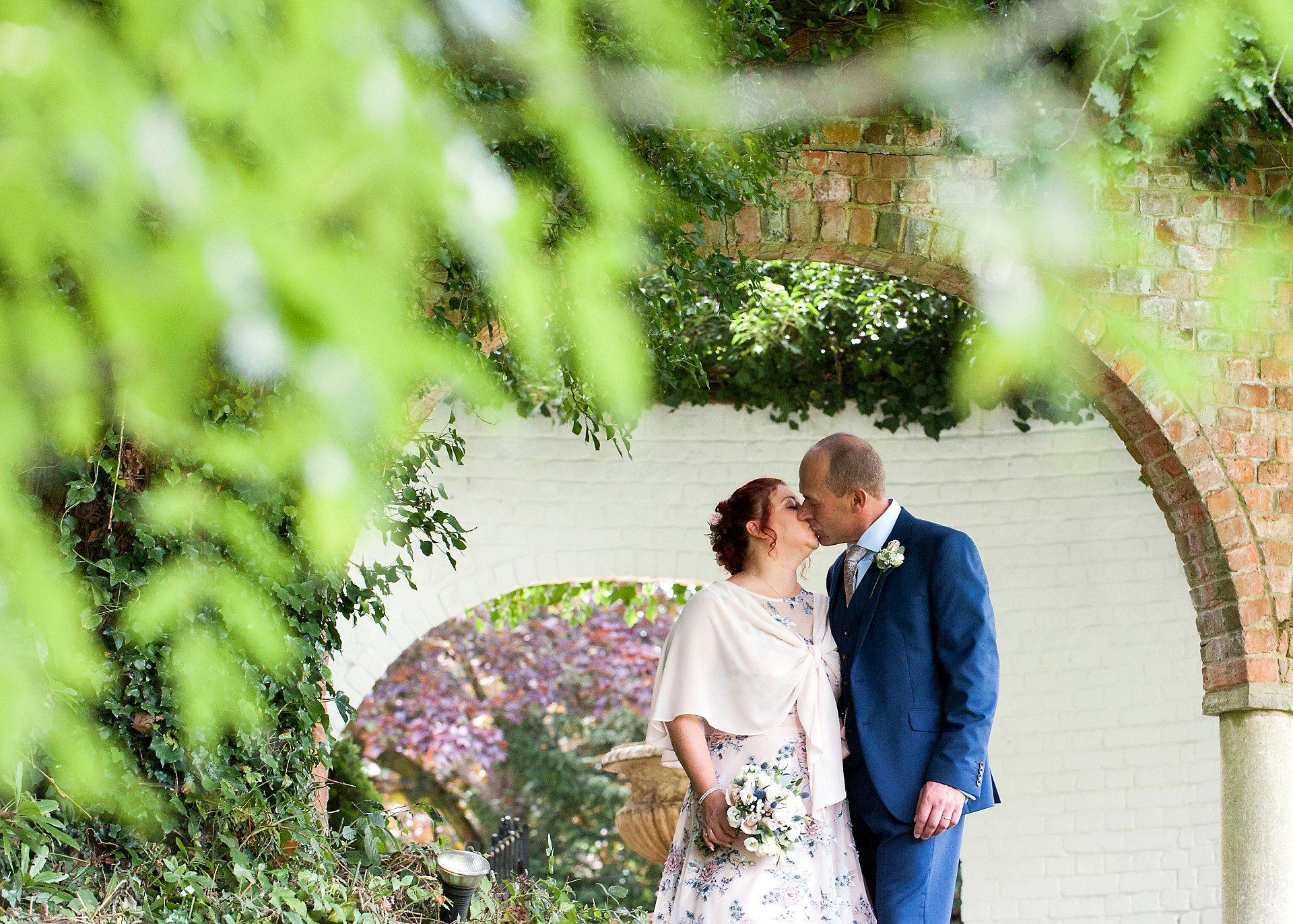 Horsham wedding venue Ghyll Manor is a stunnng 17th century country house venue perfect for weddings both large and small and here the bride and groom kiss tenderly just before their wedding breakfast