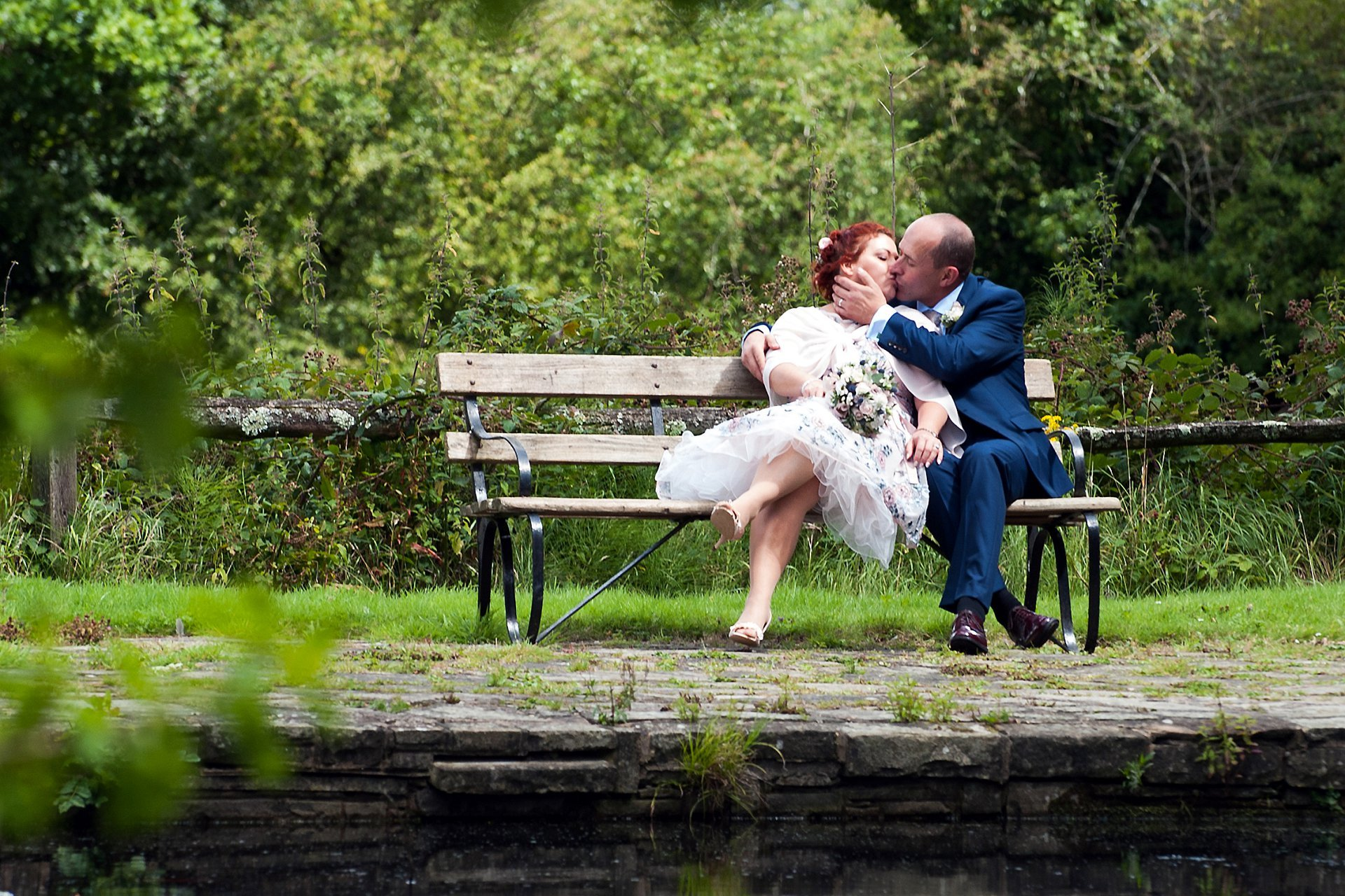 Ghyll Manor wedding photographer Emma Duggan Photography here photographs a bride and groom by the pond taking a moment to take in their recent civil marriage ceremony at nearby Park House in Horsham