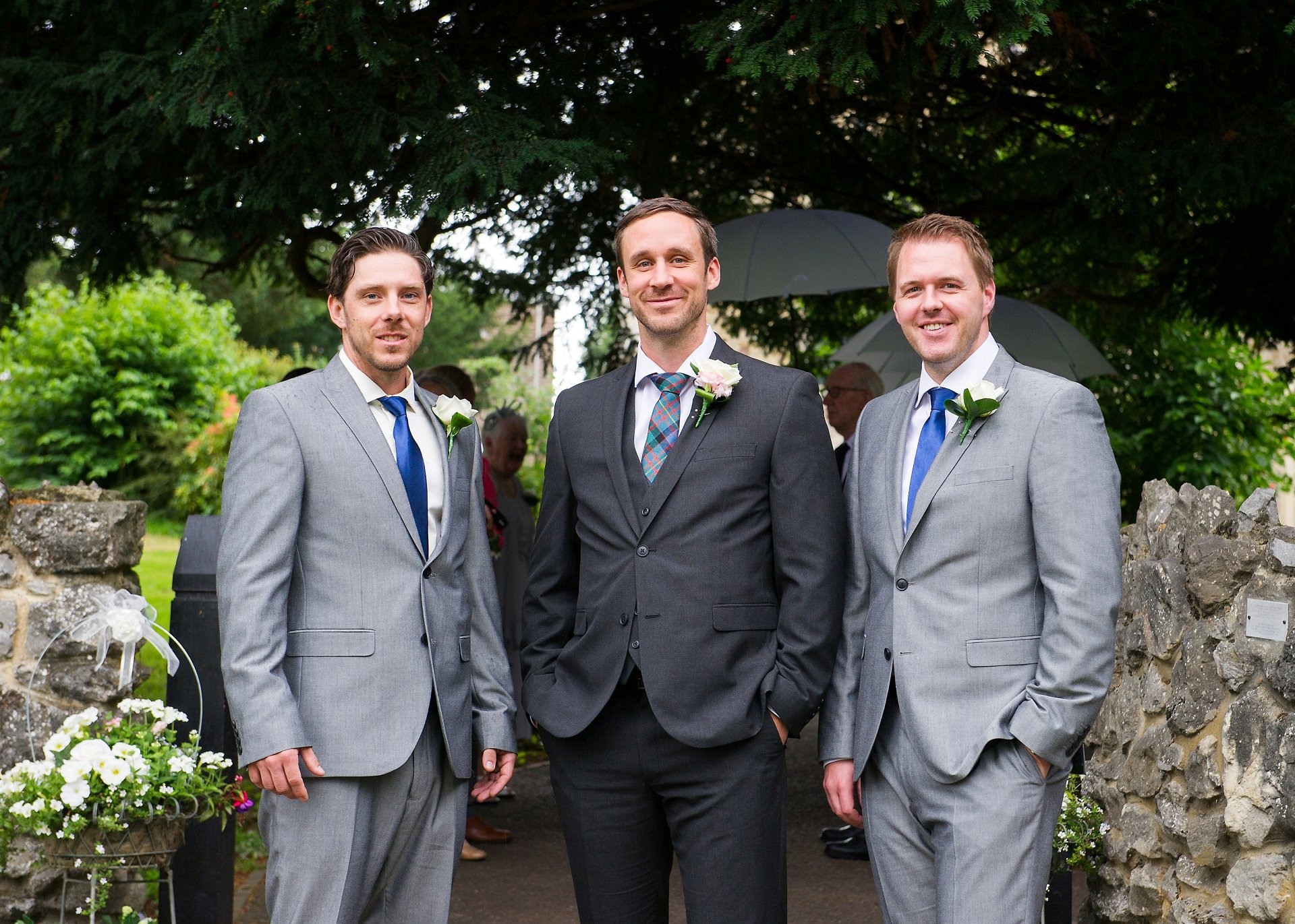 The Canadian groom and his groomsmen (ushers) outside St Peter's Ditton in smart grey suits, tartan and blue ties and rose buttonholes