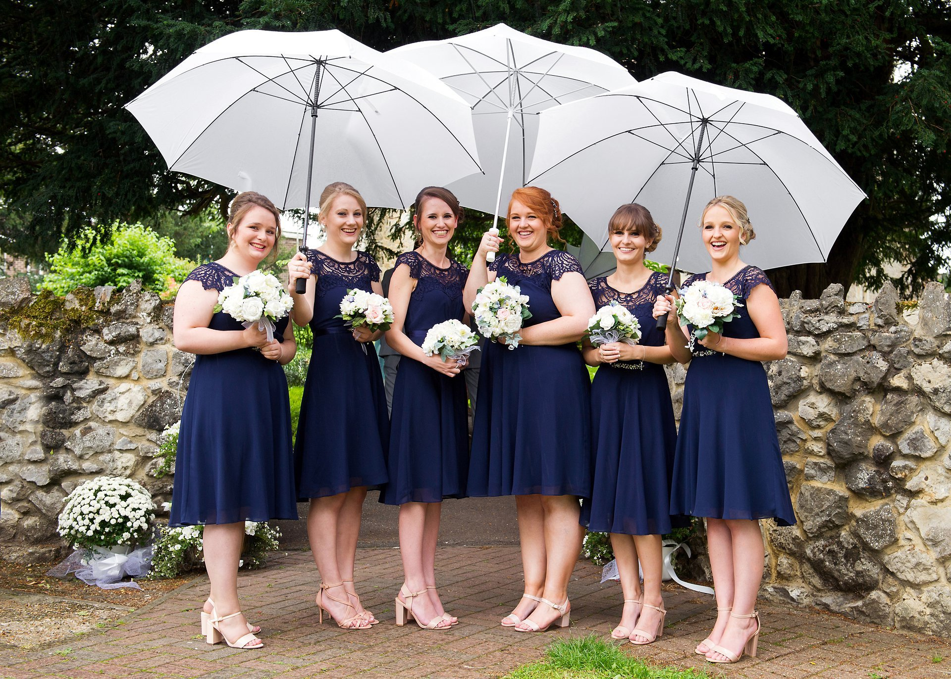 The bridesmaids for Sarah's wedding day wearng pretty navy blue just below knee-length dresses and holding white umbrellas