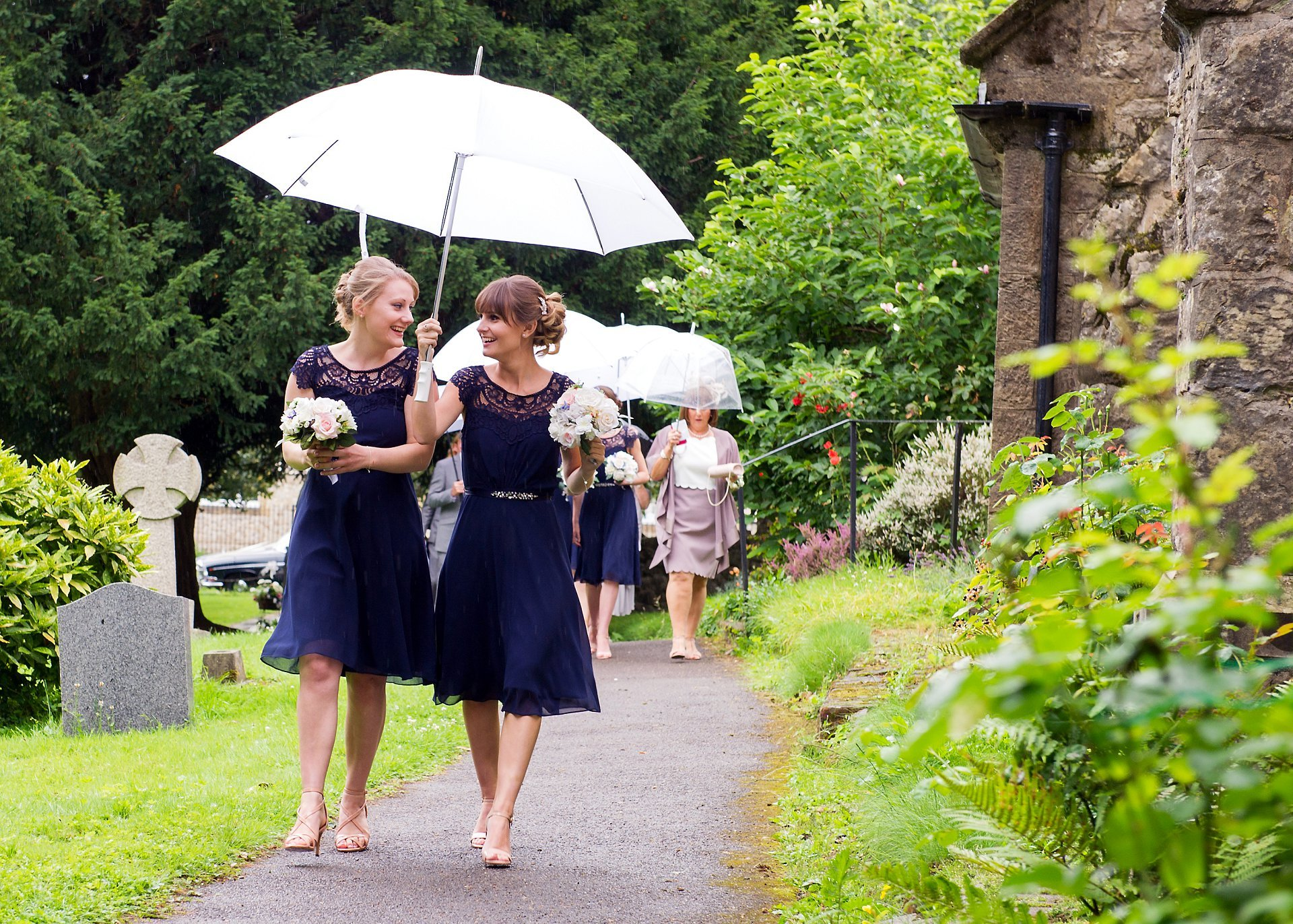 The bridesmaids walking to Church on a rainy Summer wedding day in Kent