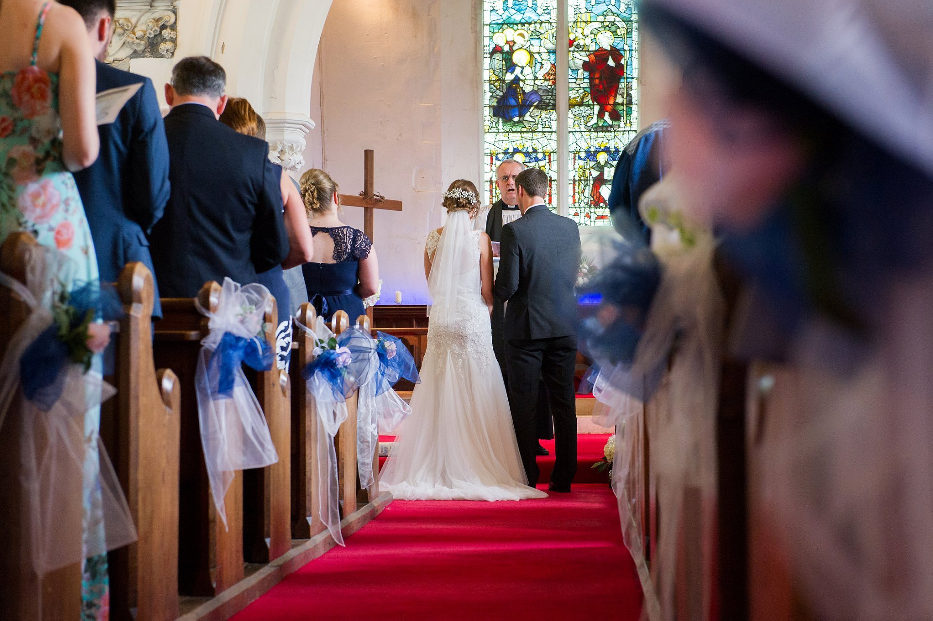 The bride and groom during the marriage blessing ceremony seen through the pretty blue and white pew end bows