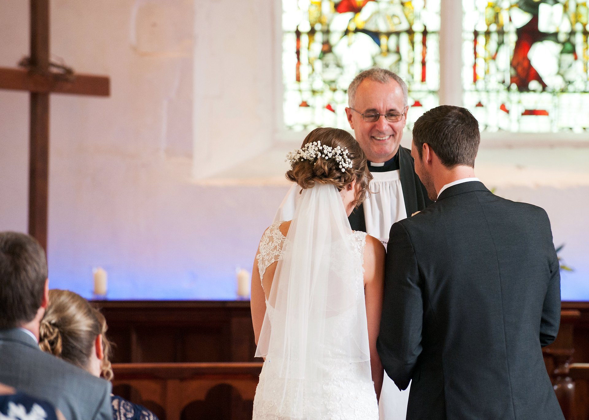 The vicar Ross Terranova smiles at the couple during their wedding blessing ceremony at St Peter's Ditton