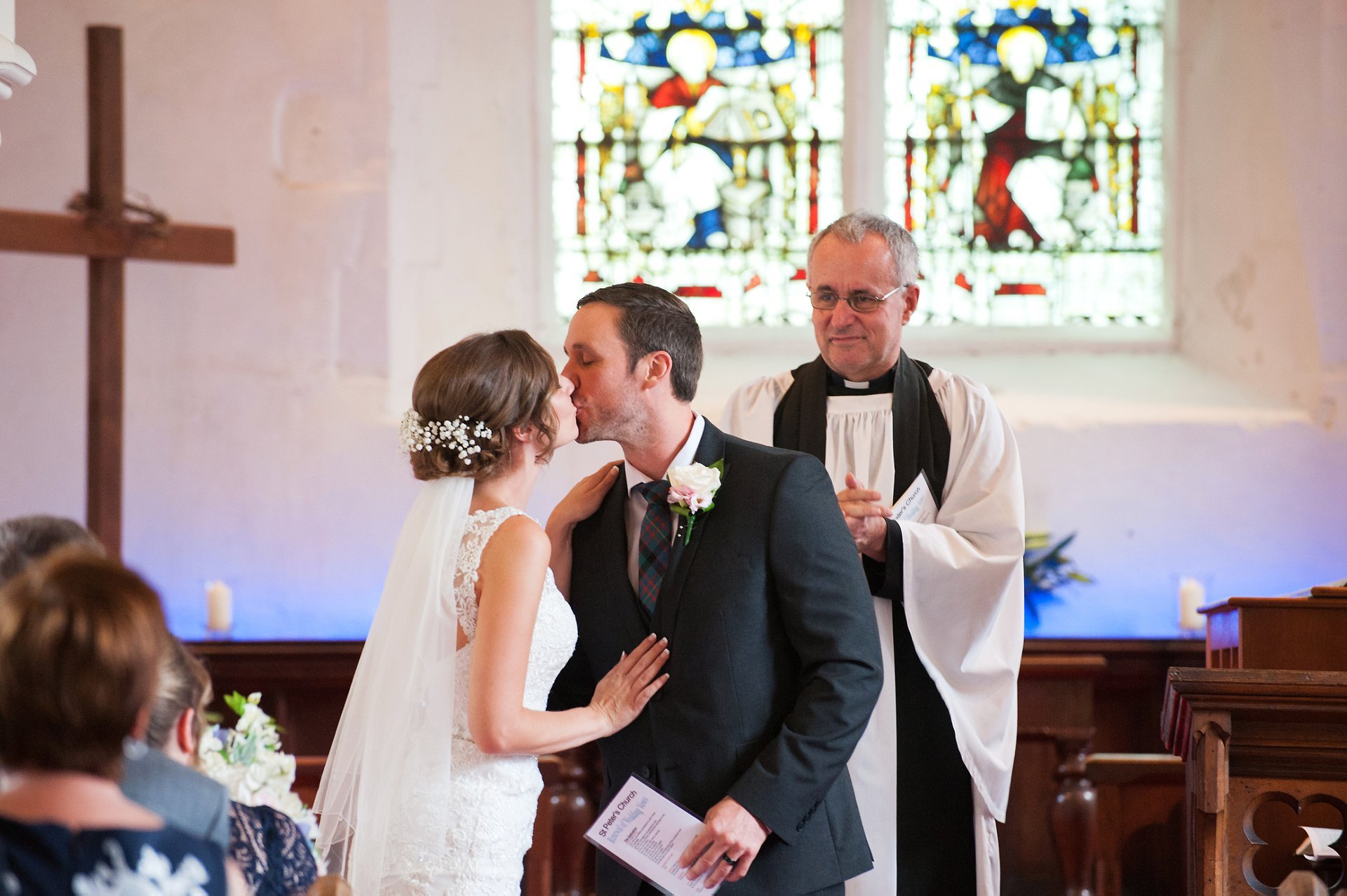 Ross Terranova at St Peter's Church Ditton smiles as the bride and groom kiss at the end of the marriage blessing of thie young British and Canadian couple, both teachers and heading to live in Canada. Their reception was at gorgeous Kent venue Leeds Castle in neaby Maidstone