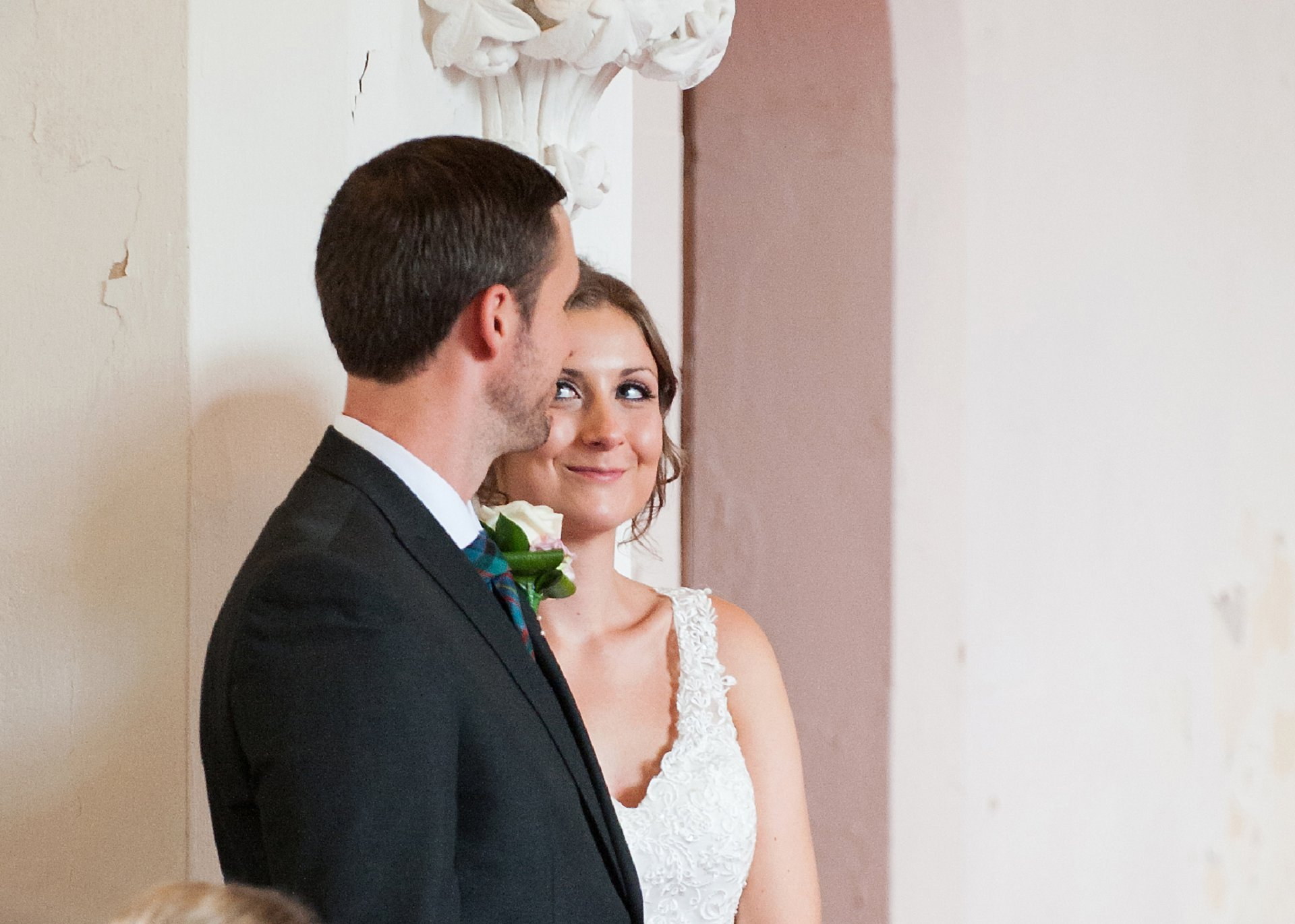 Bride, Sarah, smiles at her groom, Brady, during the wedding blessing service at St Peter's Ditton